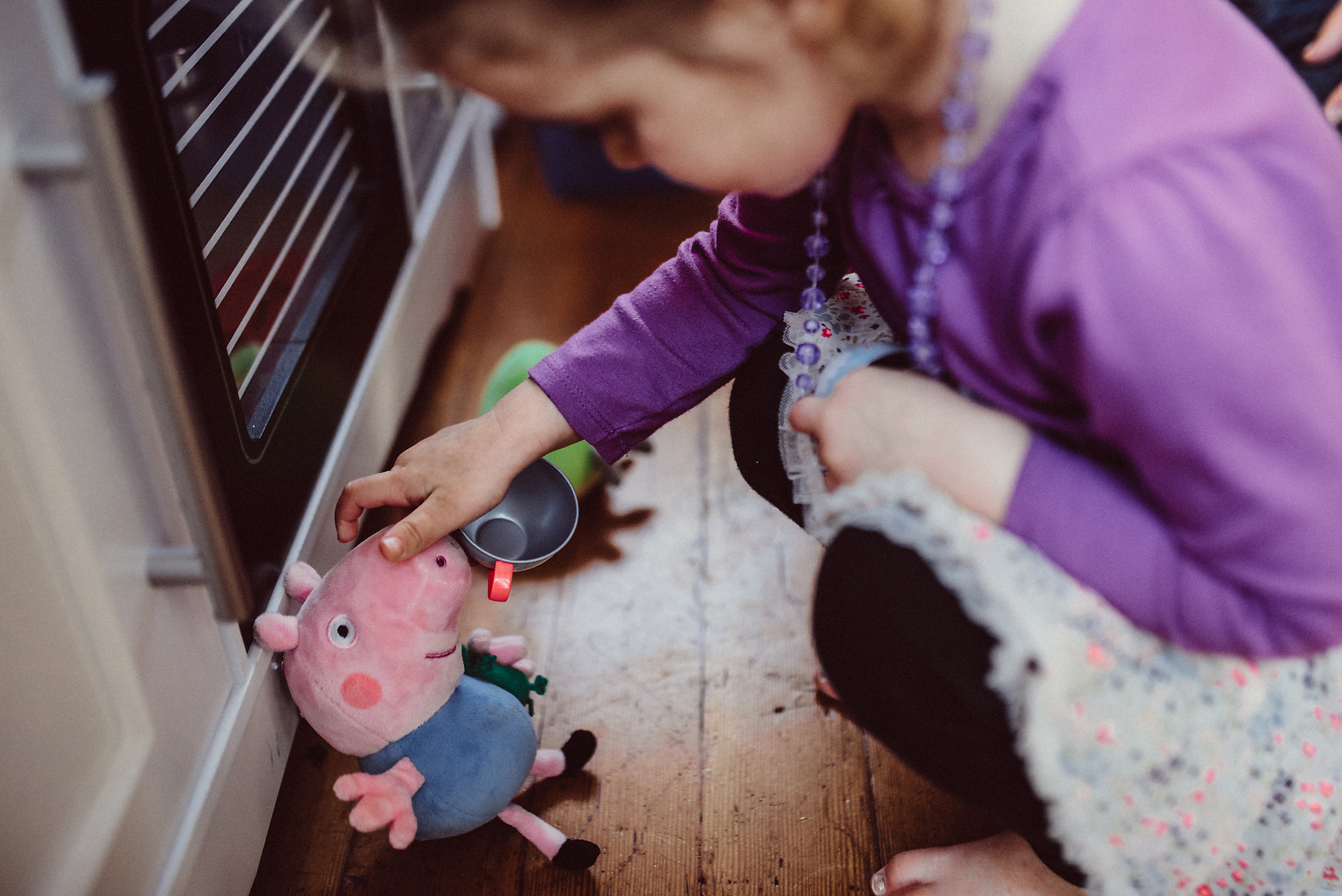 Little girl playing with stuffed pig in kitchen play room