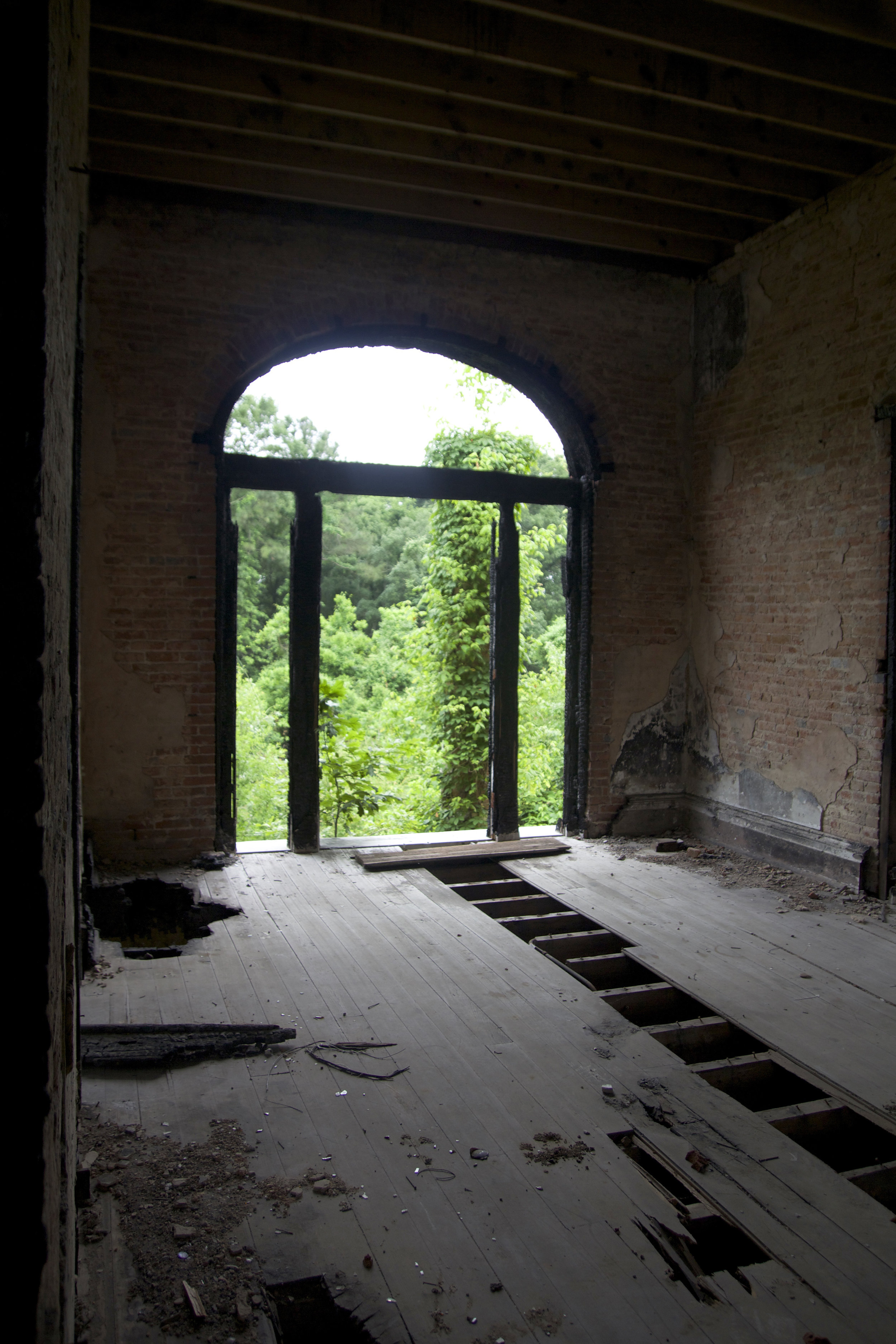 The view from the second floor central hall. The exposed beams from the ceiling and surrounding the door are damaged from the the 2002 fire.