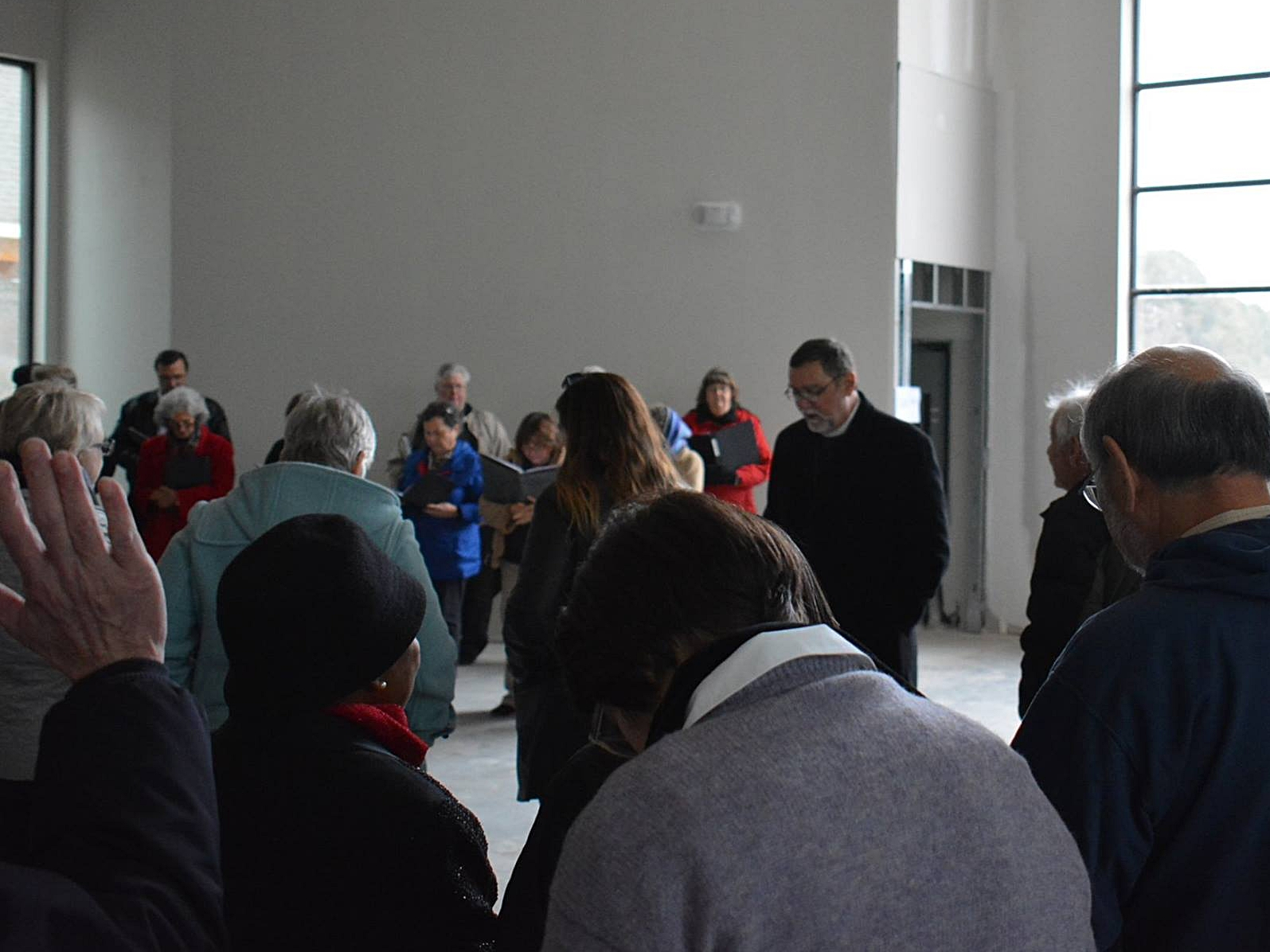 Prayer in the newly built, unfurnished Sanctuary.