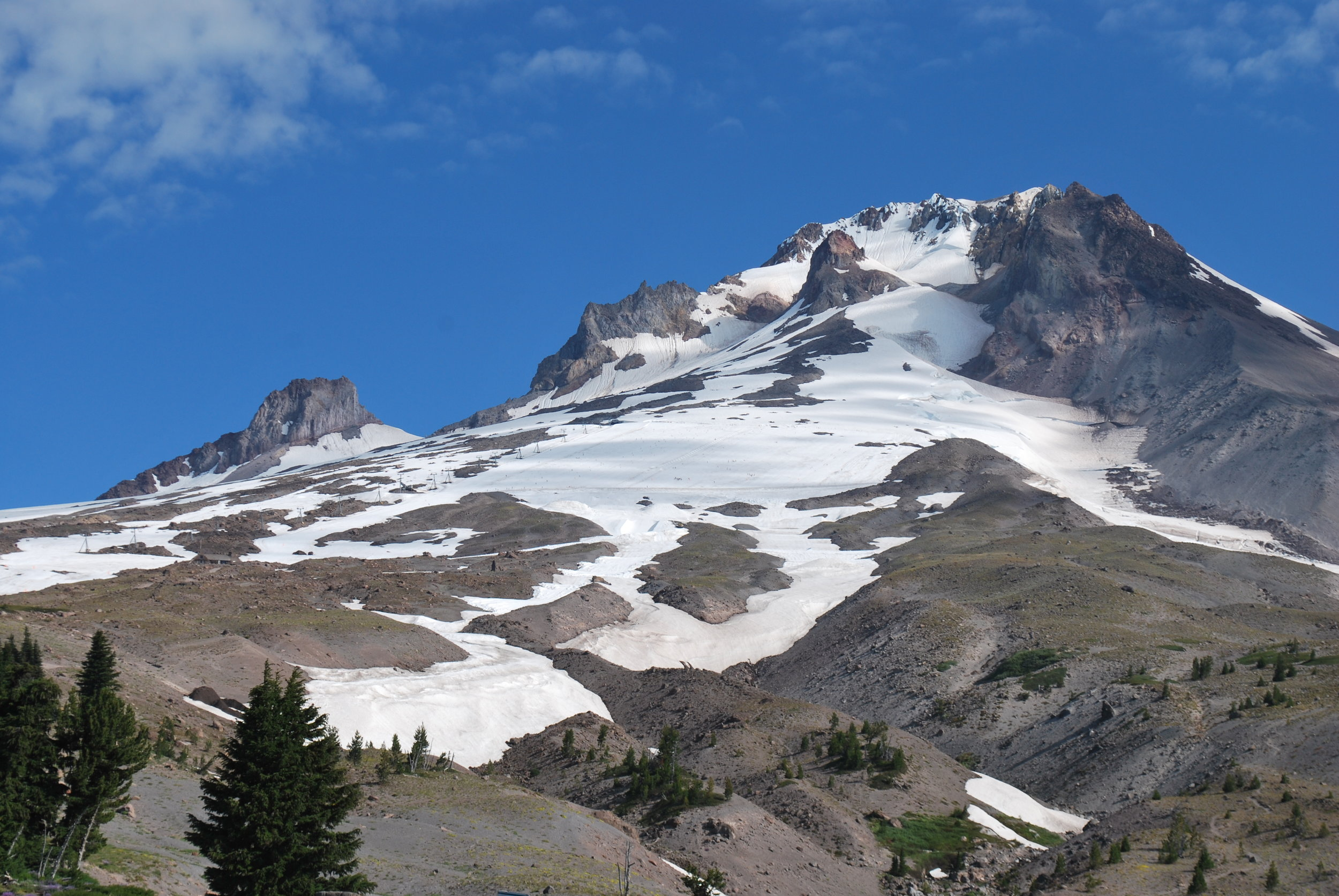 This image from Snowbrains.com shows the summer snow fields up at Timberline Lodge Ski Area. The Palmer Glacier (square-shaped) is very evident at the top of the two canyons. There is actually more snow up there now than this picture shows (this was later in a past summer). Image Courtesy: Snowbrains.com