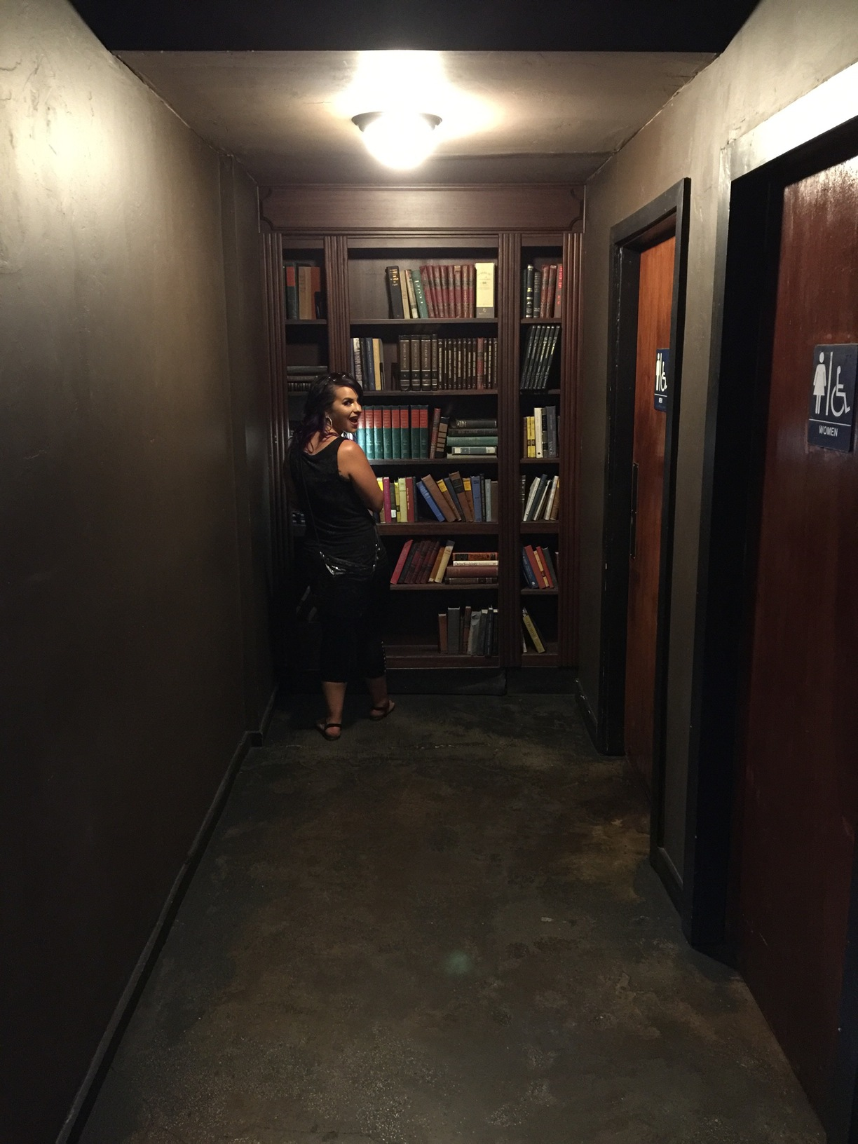 Here a patron is working on getting the false library door open at Circa 33 where a hidden, speakeasy-like bar lurks behind. Image Courtesy: Trover