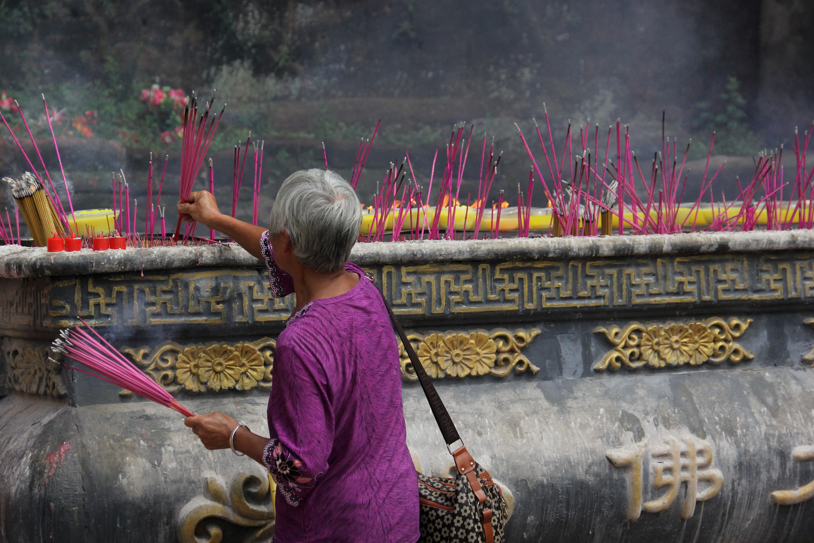Woman praying at the foot of the Giant Buddha. The purple and pink colors!