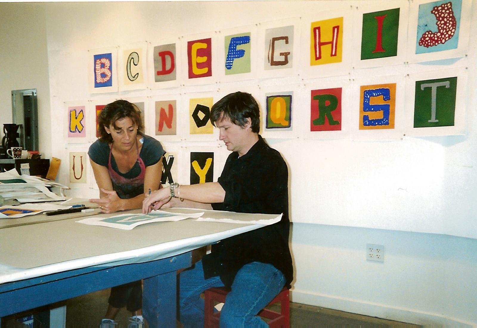 Renée Bott works with Donald Baechler on  Alphabet,  2003 Paulson Bott Press studio Berkeley CA.