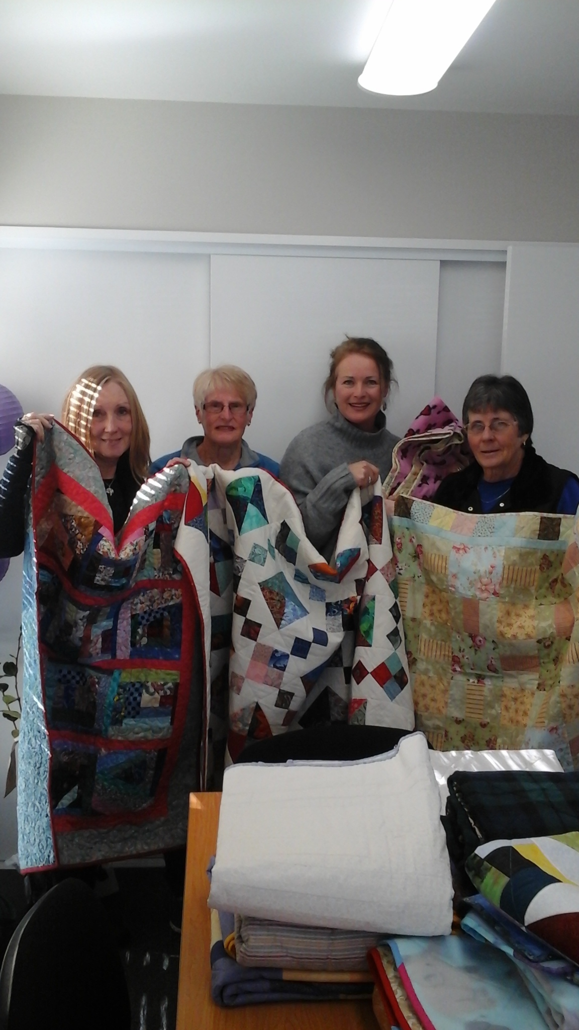 """From left Susan Arrowsmith (Aged Concern), June Mannix (NQG ), Marrit Walstra-Russell (Aged Concern), and Leone Burborough (NQG). """"Leone and June on behalf of the NQG donated a number of absolutely stunning quilts in a range of sizes to be passed on to older people in need."""""""