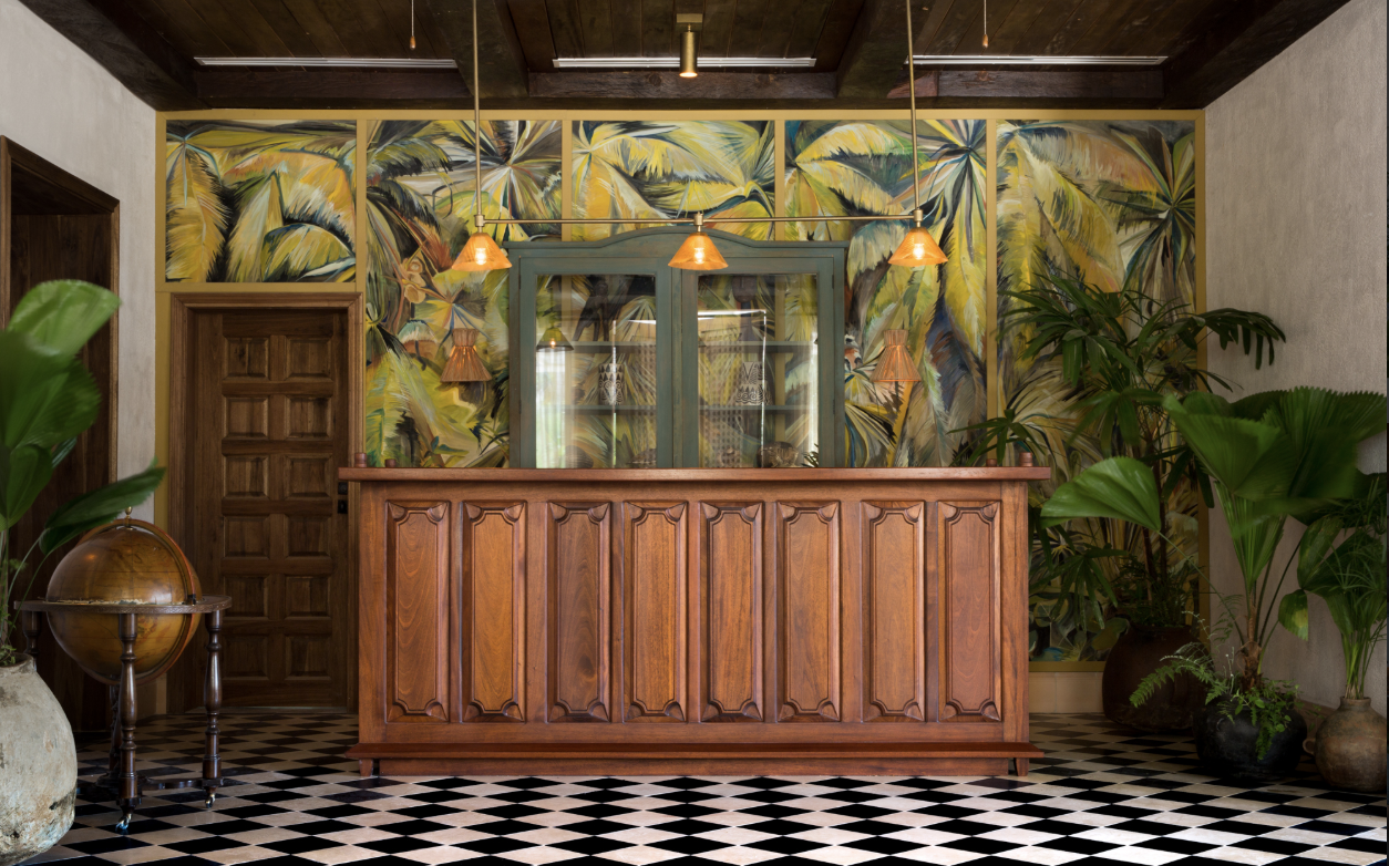 A lush palm mural by artist George Venson blooms behind the front desk at Itz'ana. Photo: Itz'ana
