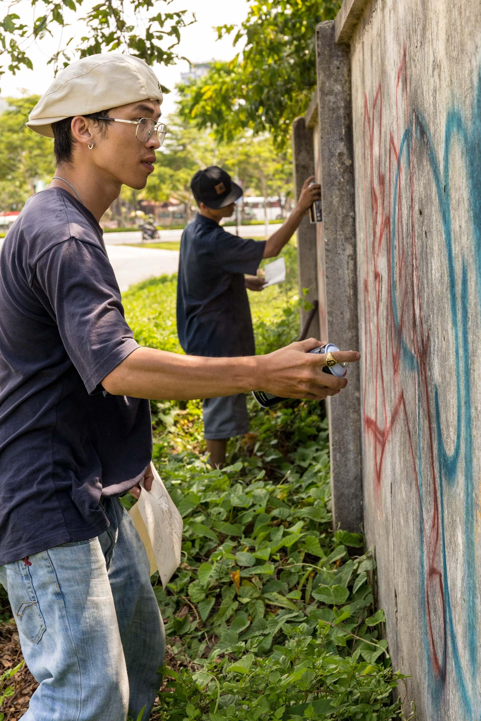 Graffiti Artists in Action in Da Nang City Centre, Vietnam.