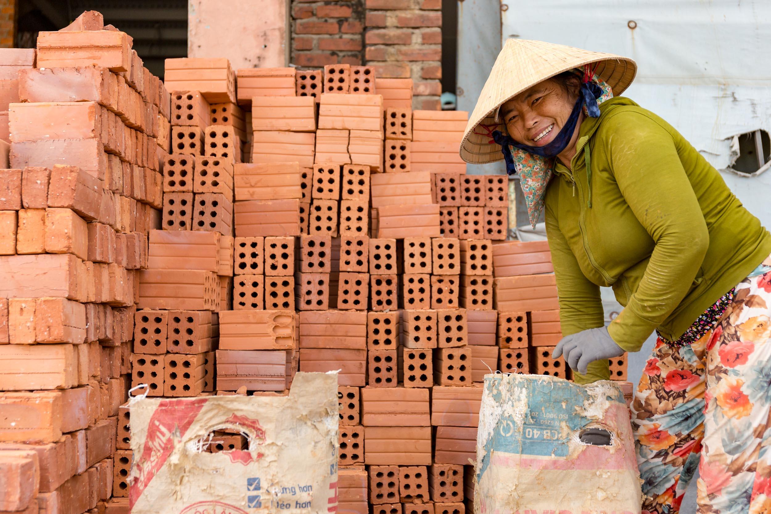 Vietnamese lady packing bricks.