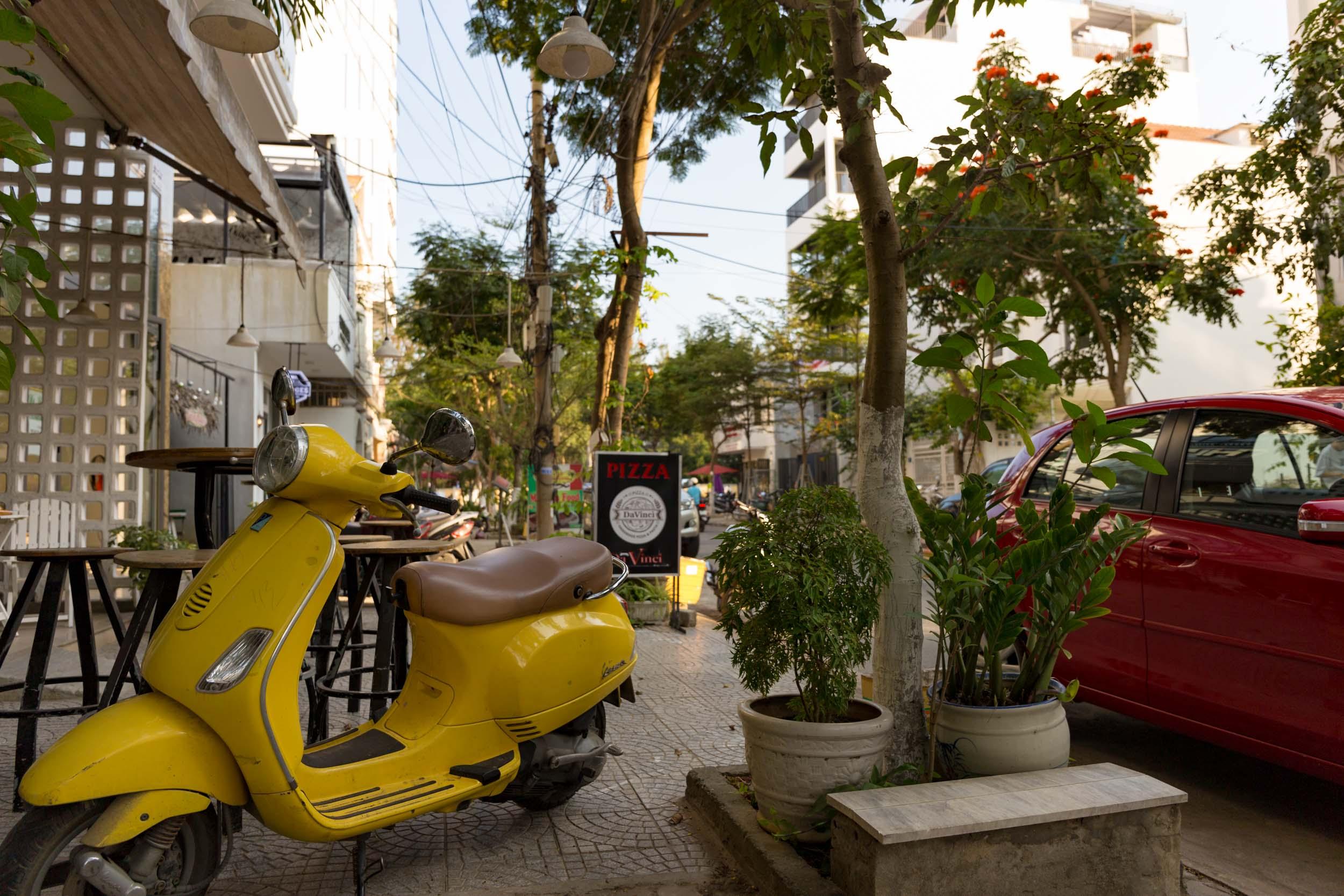 Colourful moped outside da vinci's pizza joint.