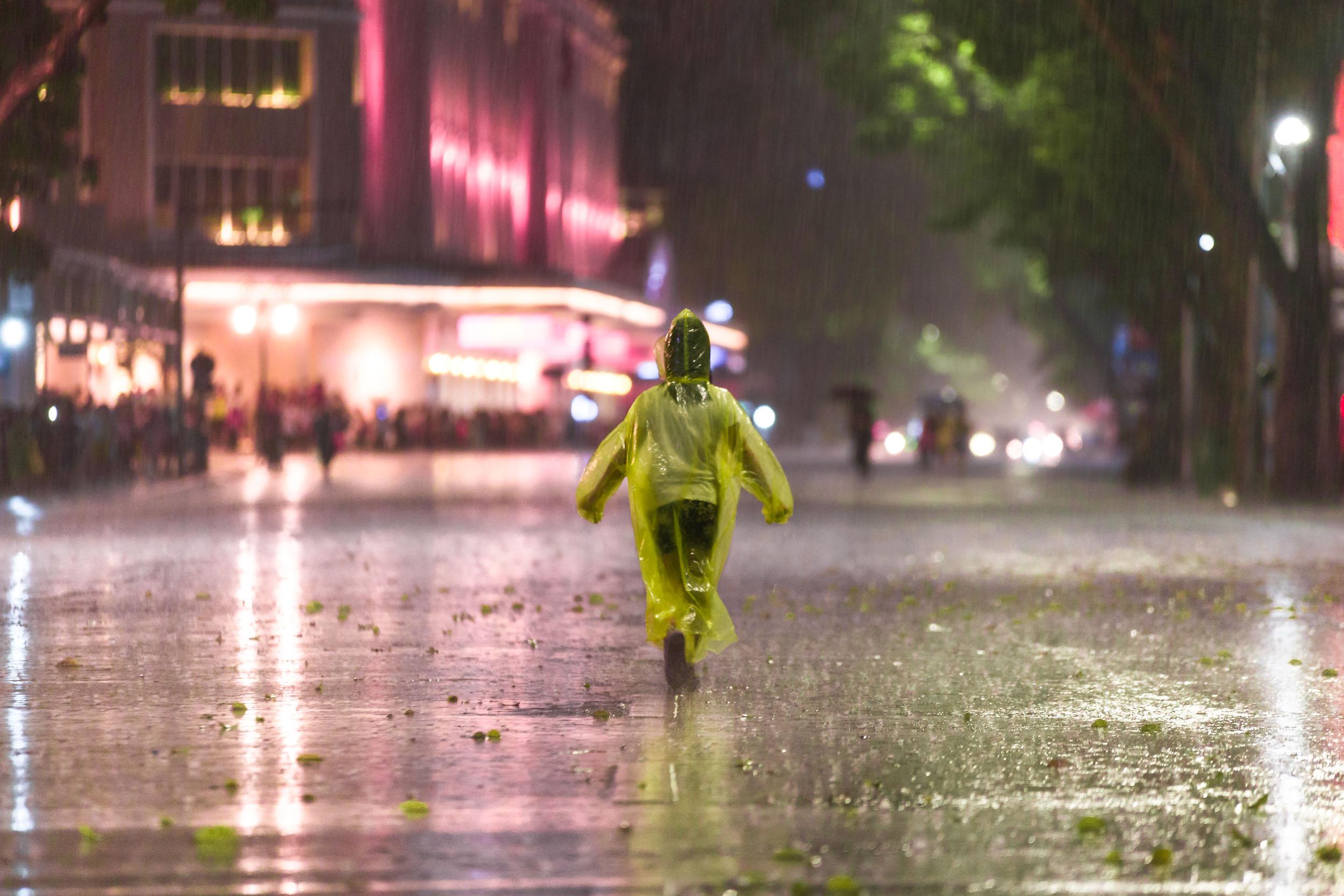 Girl on street in Poncho under heavy rain in Hanoi.