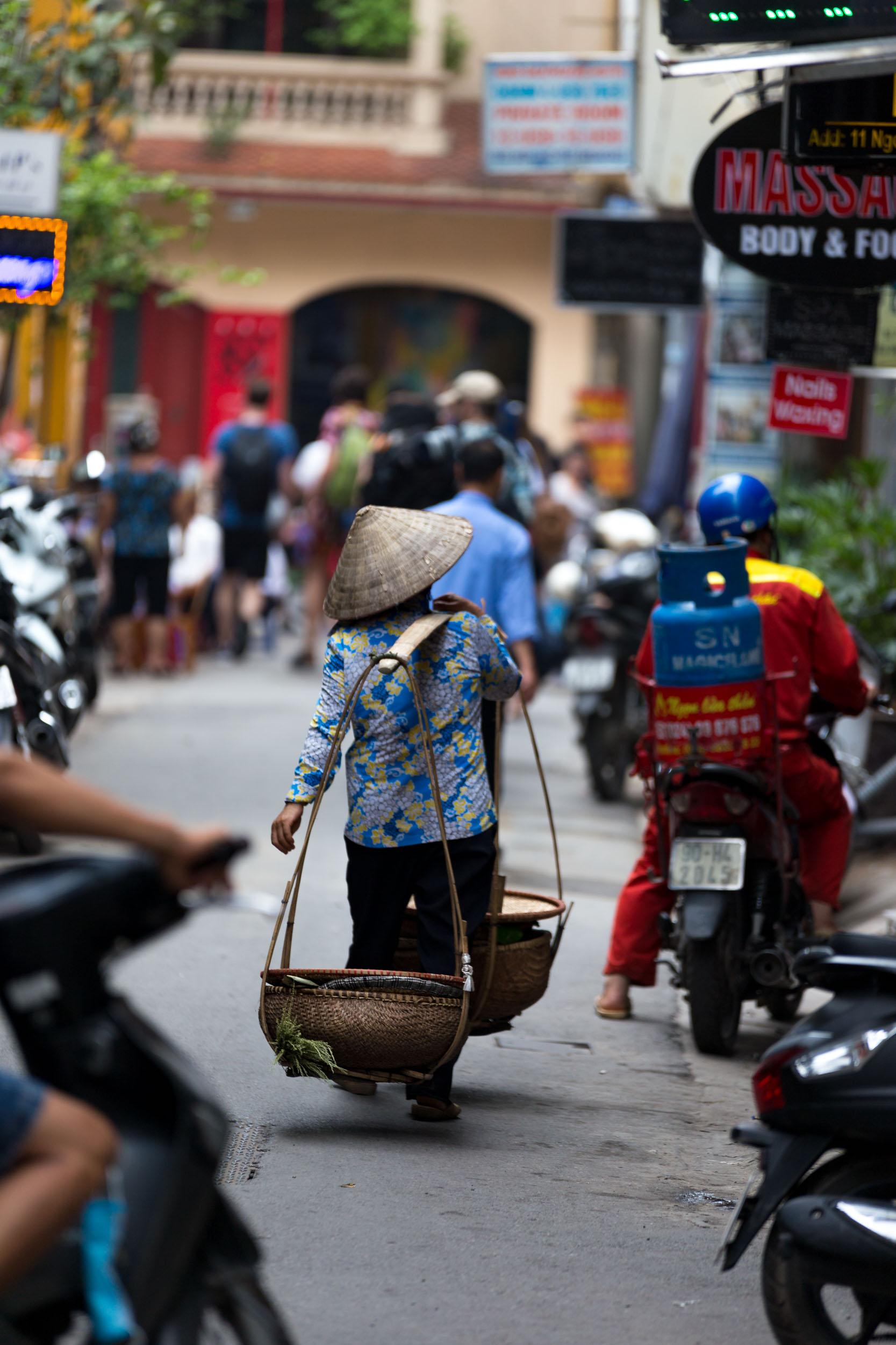 Local trade girl carries 2 baskets on shoulder rig on Hgo Huyen, Hanoi.