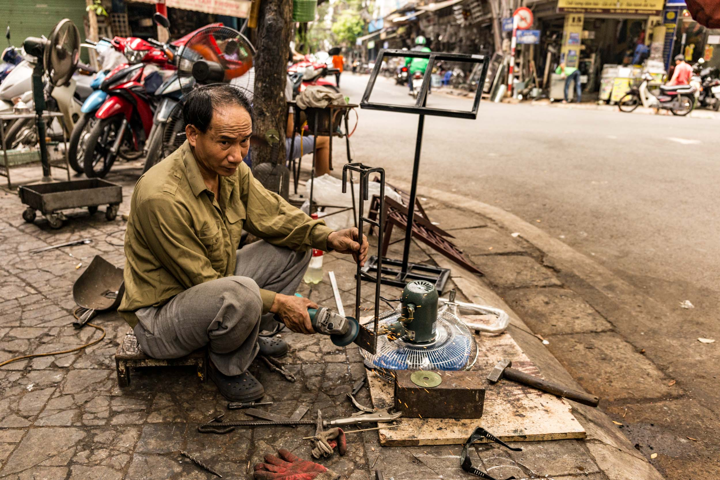 Steel worker grinding away on streets of hanoi.