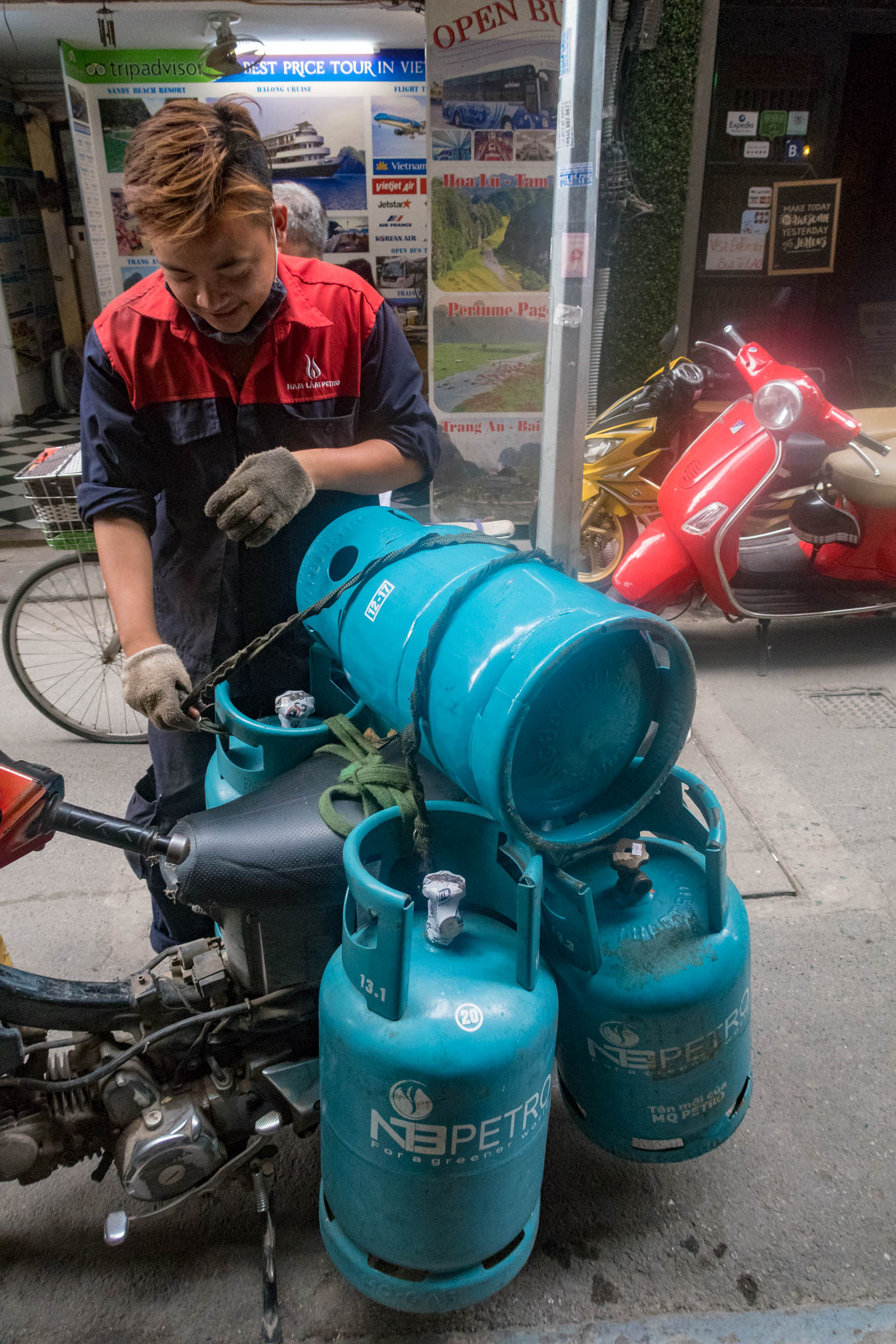Hanoian delivery driver precariously ties gas canisters to moped.