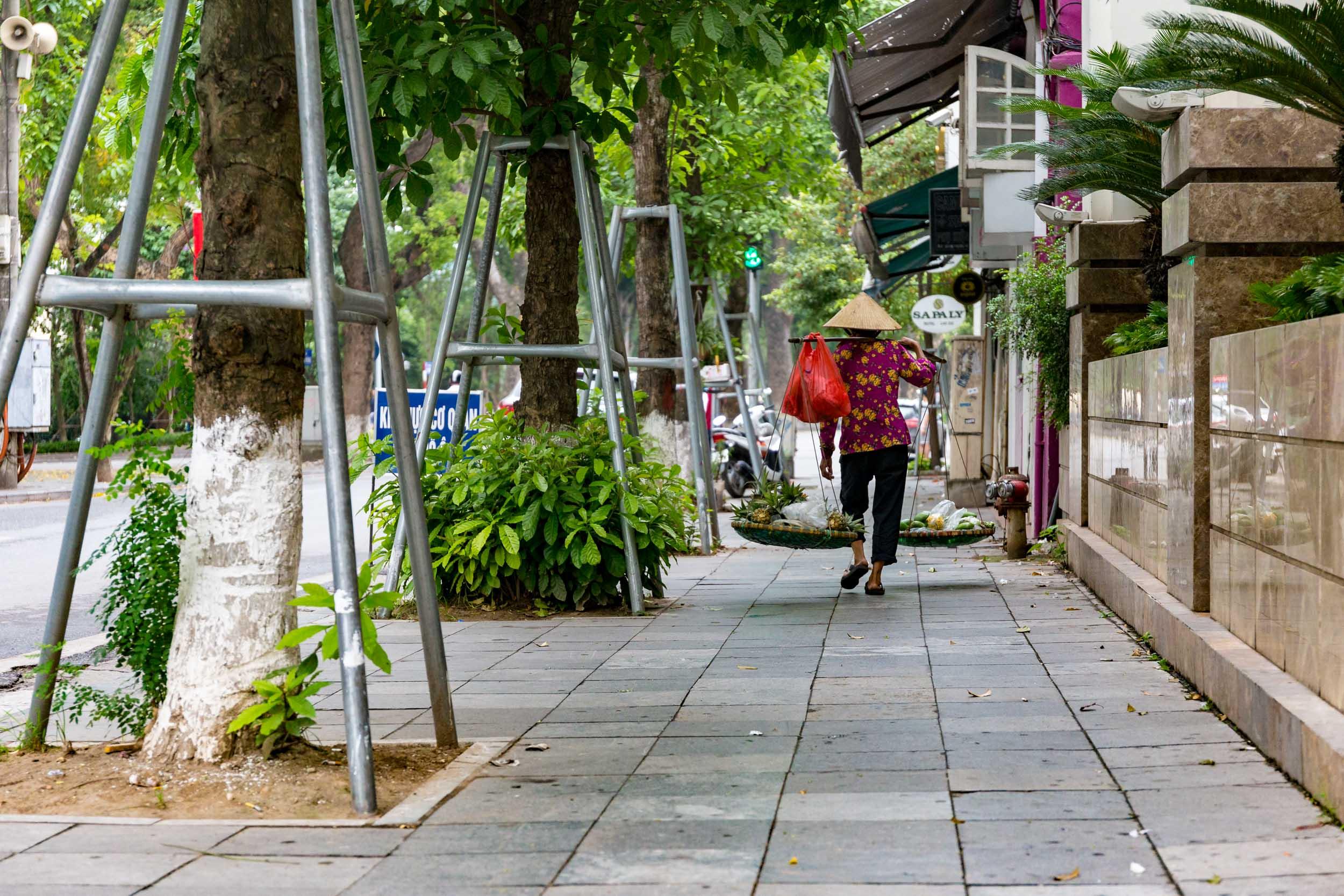 Market girl carries her baskets on shoulder in Hanoi