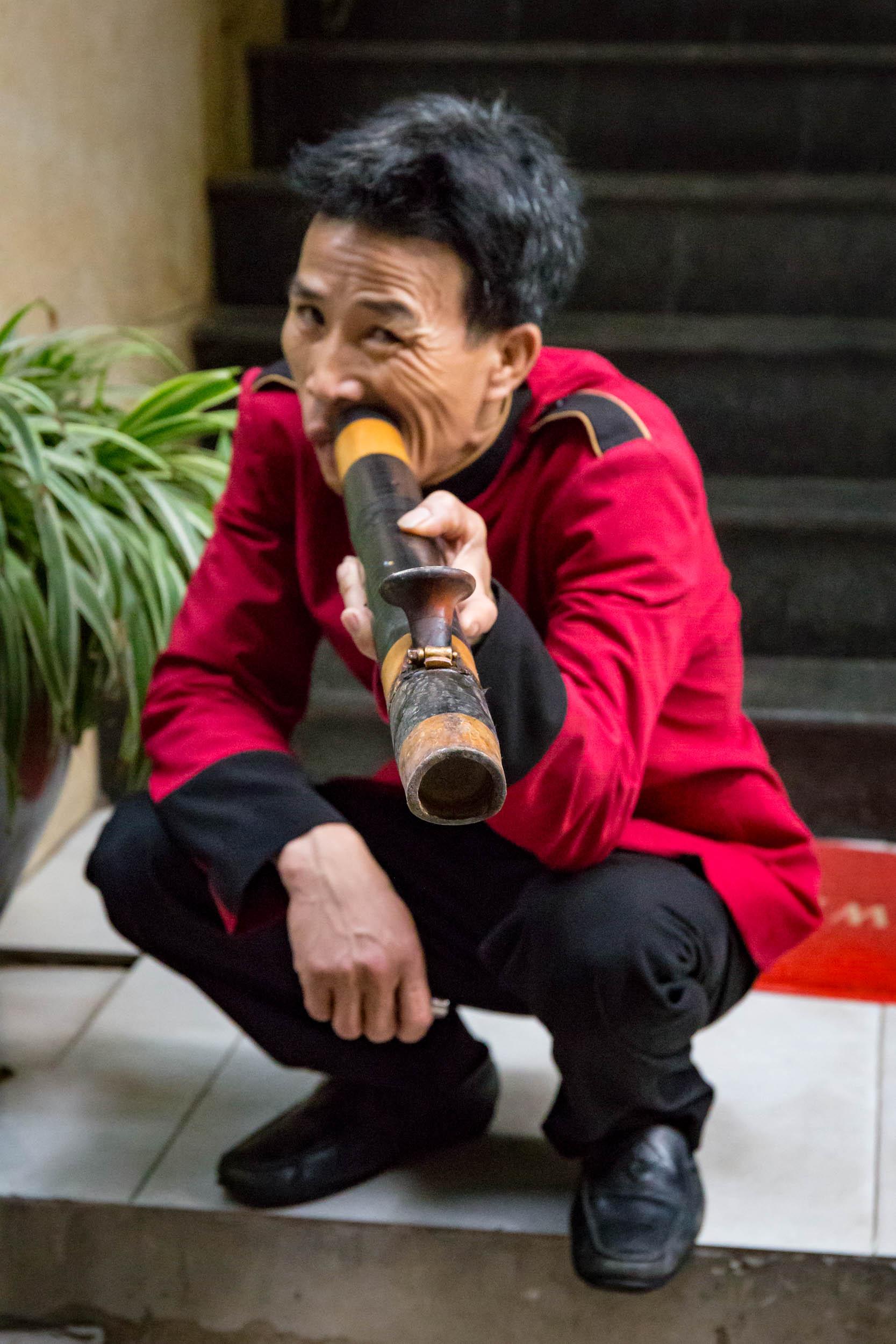 Hanoi bell boy smokes his pipe.
