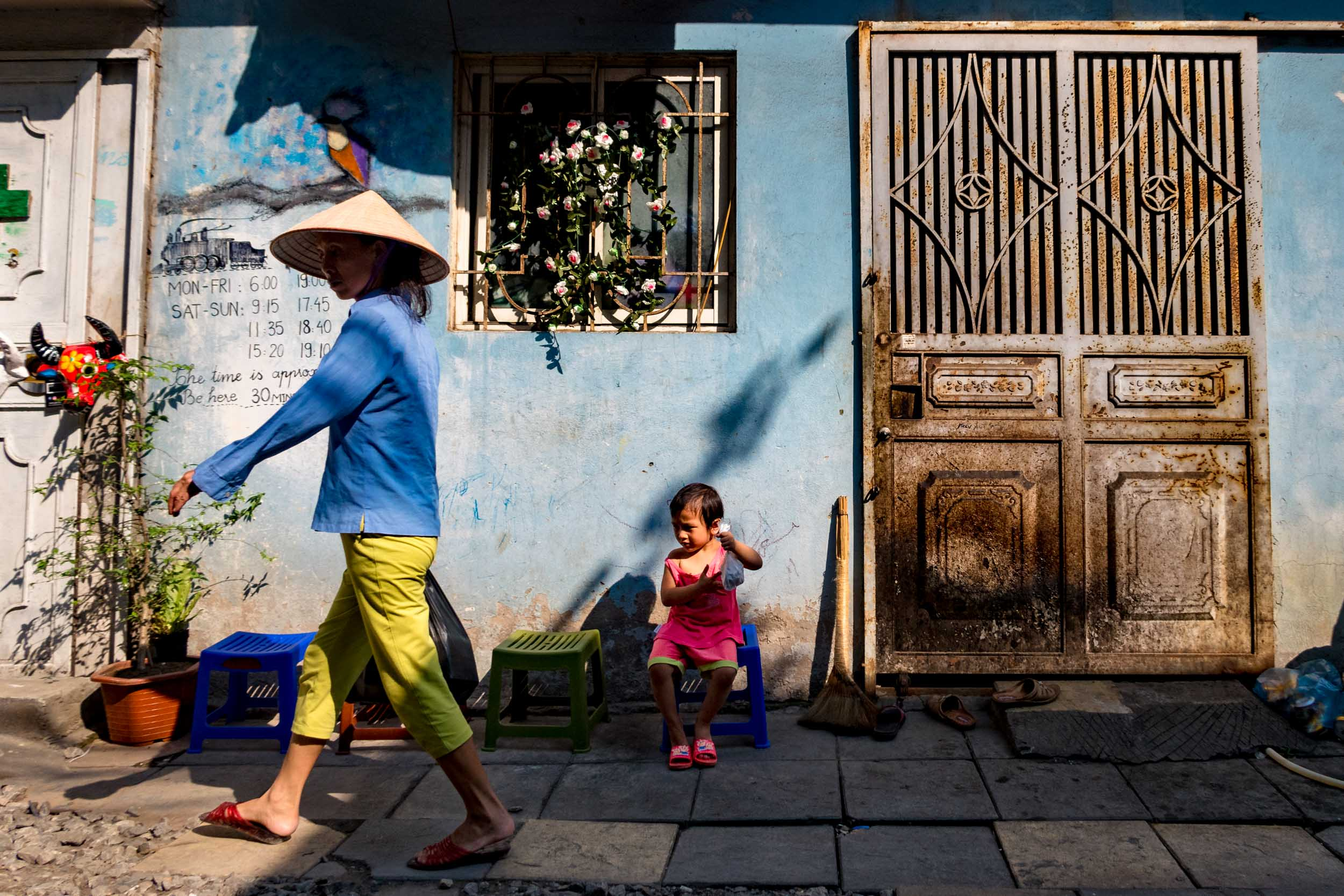 Vietnamese woman strolls along train track in Hanoi.