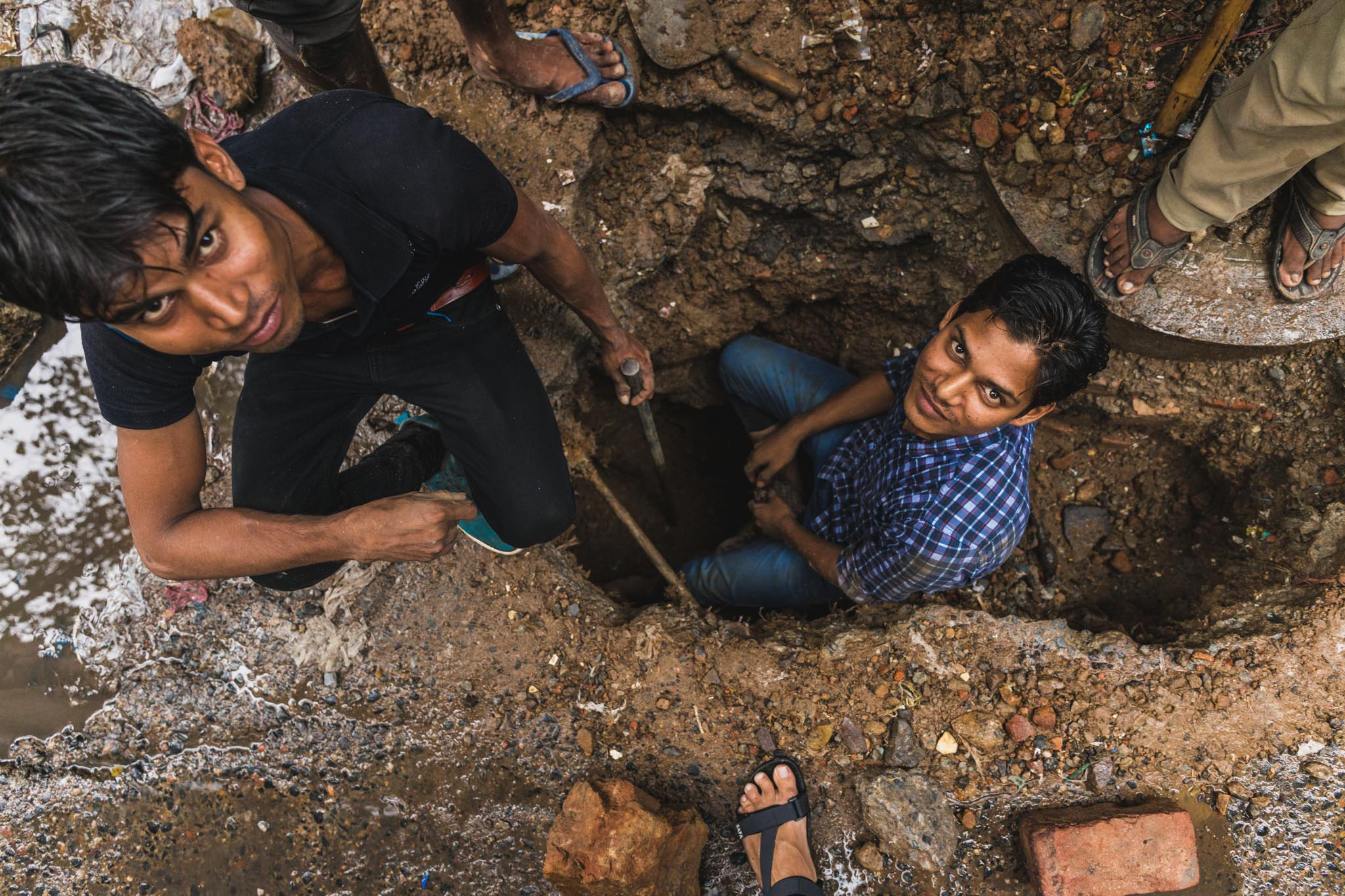 Indian street workers in hole.