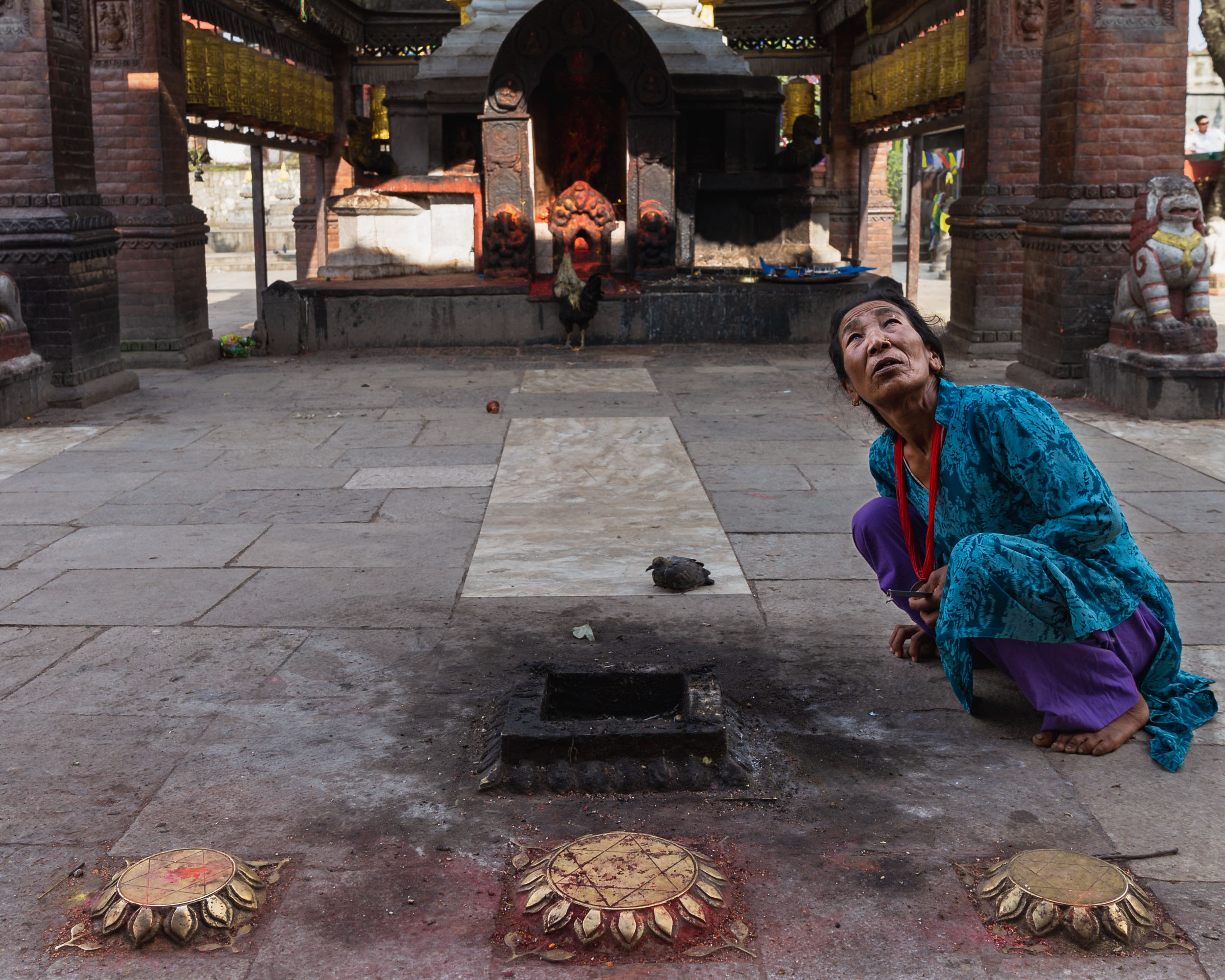 Tibetan lady crouches curiously.