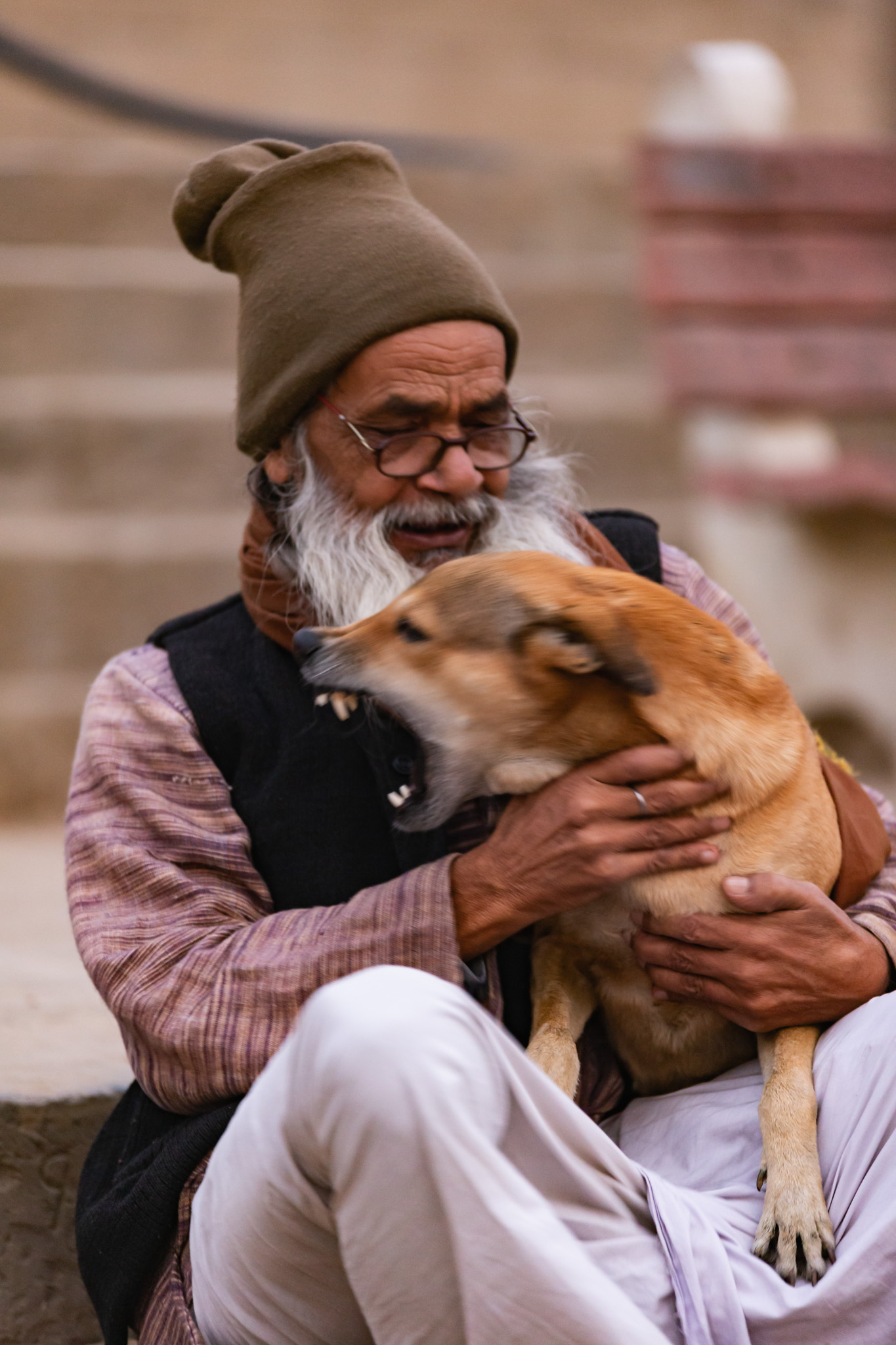 Indian man holds aggressive dog.