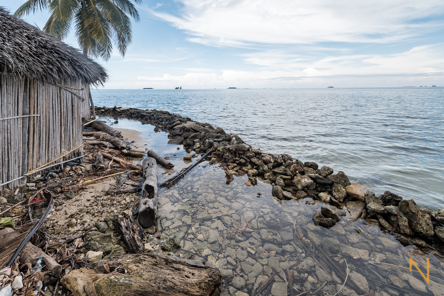 A rudimental barrier made with a mix of rocks, dead corals, sand and trash.