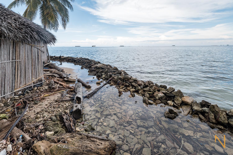 Una barrera rudimentaria hecha con una mezcla de rocas, corales muertos, arena y basura.