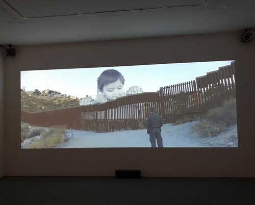 Photograph captured of a short film at Perrotin Gallery (NYC) about JR's installation at the U.S.-Mexico border in 2017. A baby boy peers over the American border from Mexico.