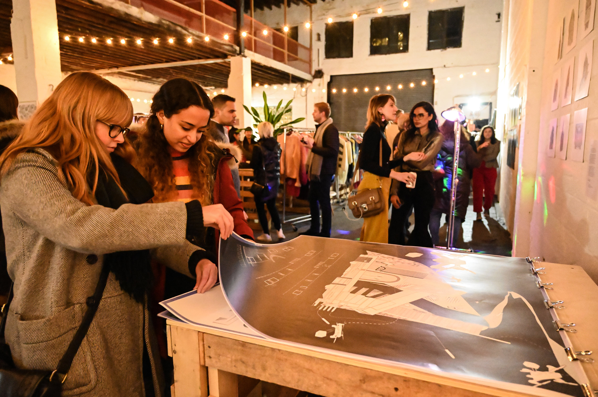 Guests viewing architectural drawings by Jon Levine at SUSTAIN's  Eco-Art Showcase  in January.