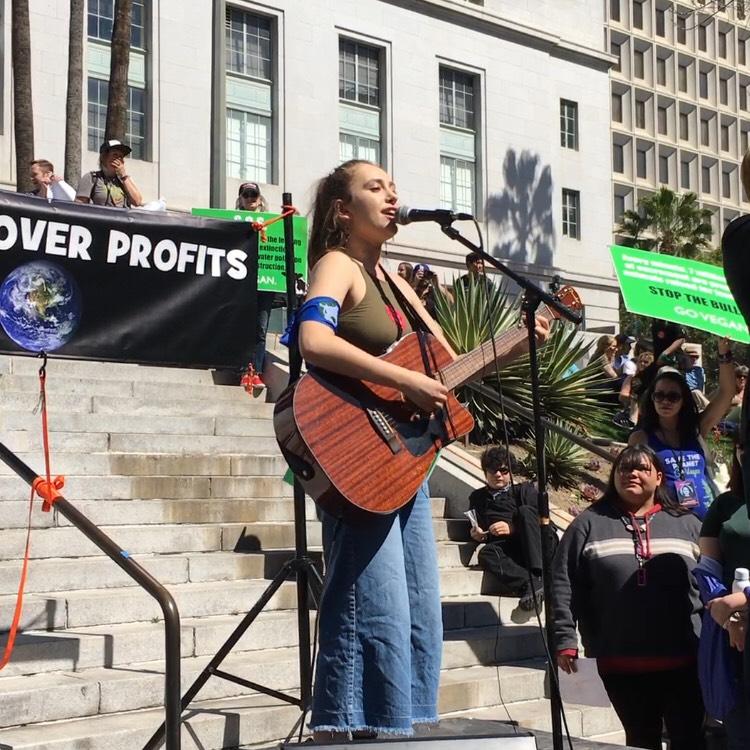 Organizer Arielle Martinez Cohen singing an original song during the strike.