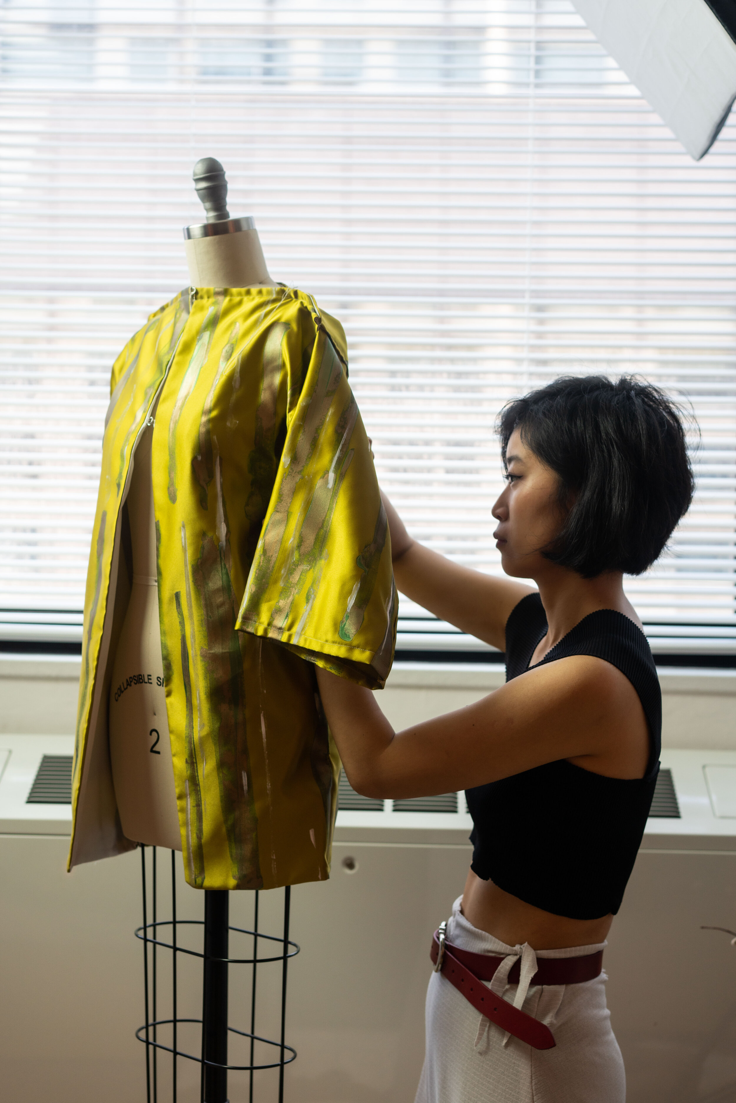 Xu in her studio making adjustments to one of her current pieces, featuring straight lines more aesthetically similar to the Japanese kimono, which much of zero-waste technique is based on.