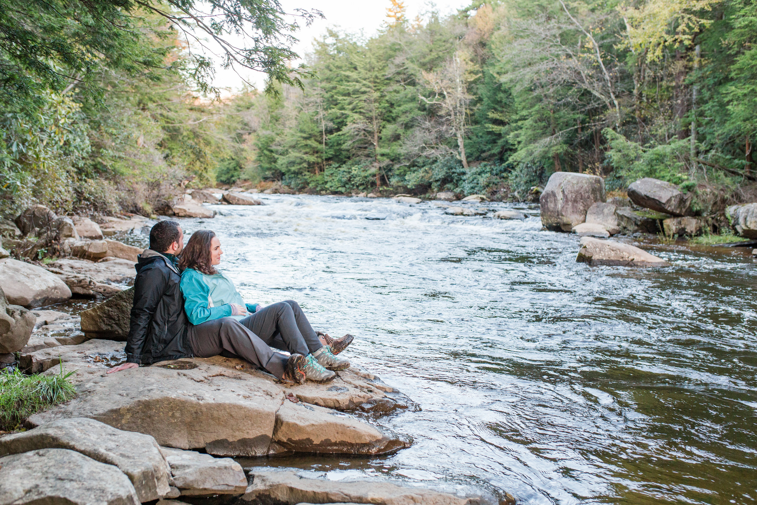 hiking couple reclines on rock beside river, thomas, wv