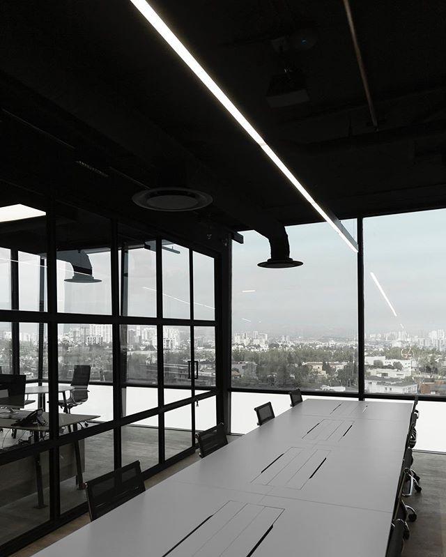 Líneas de luz iluminan las mesas de trabajo, diseñadas a medida por @cotidianomx .