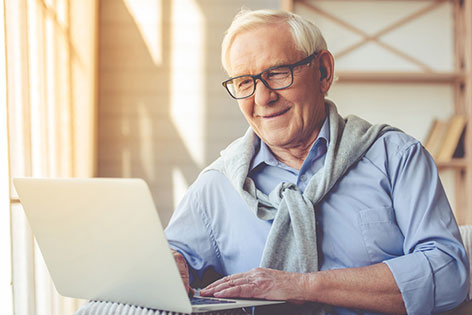 Older man using a laptop.