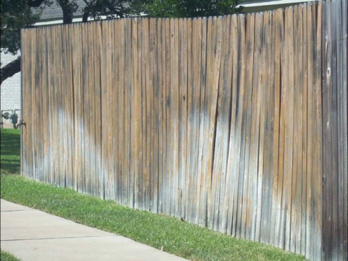 Example 3: Violations include washed-out stain, warped pickets, and a leaning section of fence.