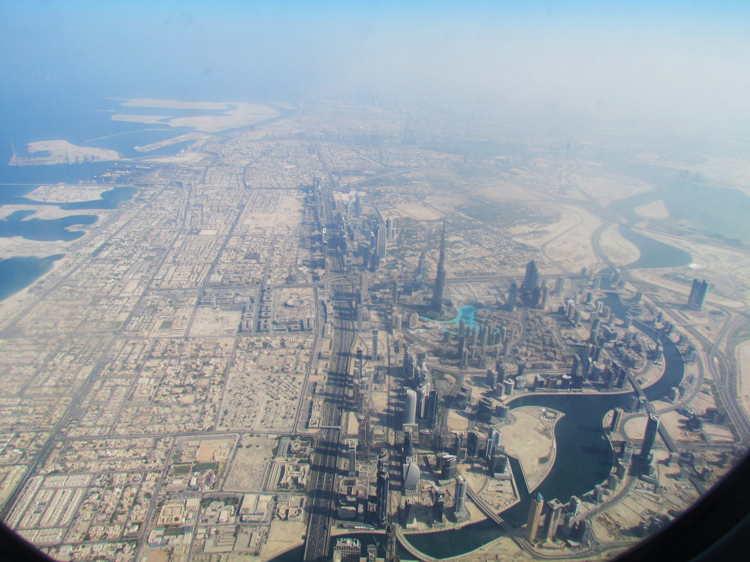 Layover in Dubai. We flew over the buildings of the city including the Burj Khalifa. Here you can see the blue pools at the base of the building.