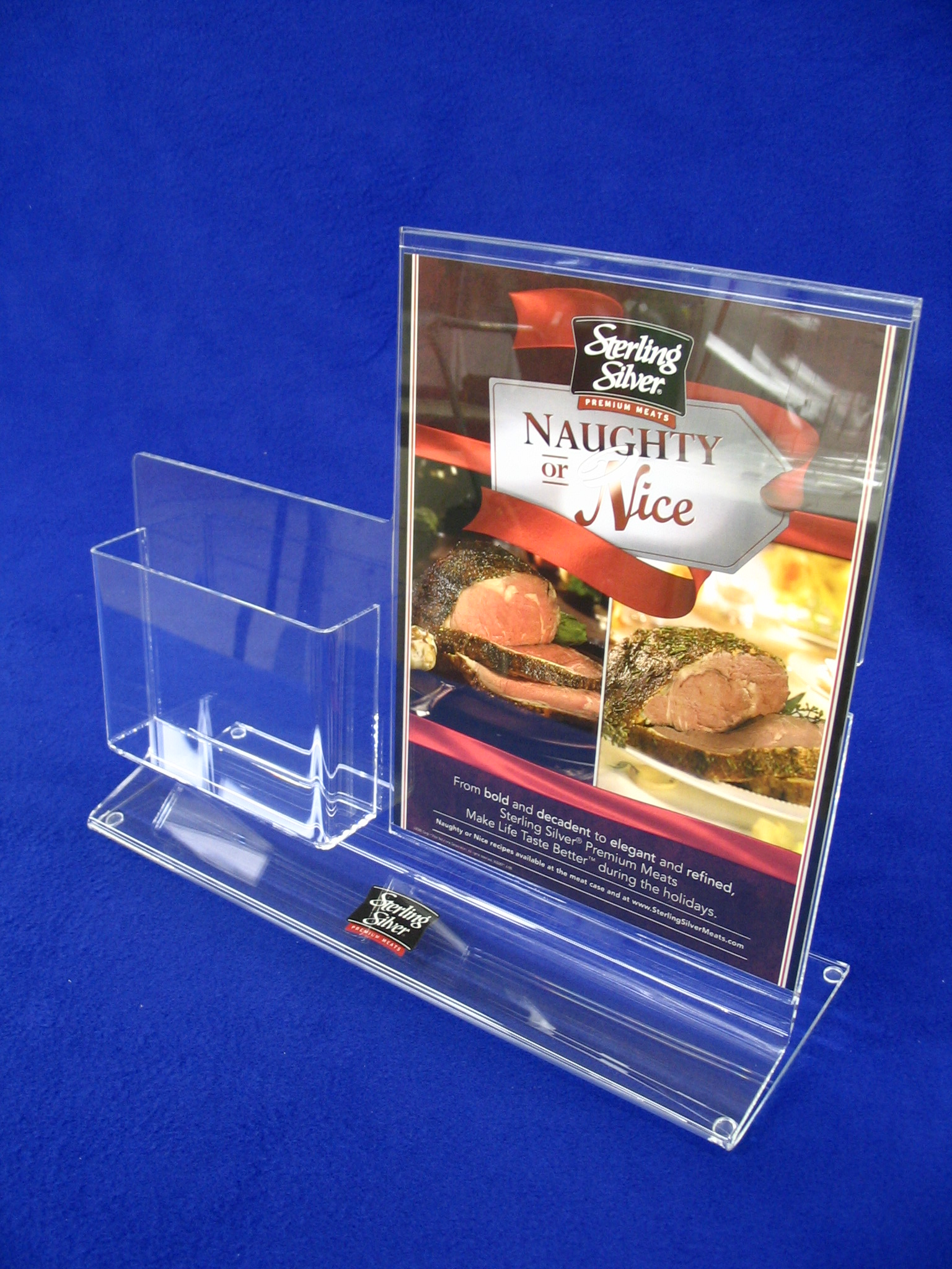 """Desk Top Literature Display   Item #  DSKTL  Price:  Varies with size Desk Top literature display with graphic sleeve and combination card pocket. Constructed from 3/16"""" and 1/8"""" clear acrylic. Sample shown has reversed 3 color logo for brand recognition. Brochure holder and pocket have polished edges."""