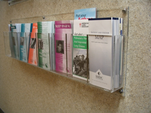 Wall Mounted Pamphlet / Literature Holder   Item #  WMP  Price:  Varies with size We fabricate a variety of wall mounted holders to fit your wall sizes and specific needs. Units can have fixed or movable dividers which can adjusted as your product information changes. Several material choices are available.