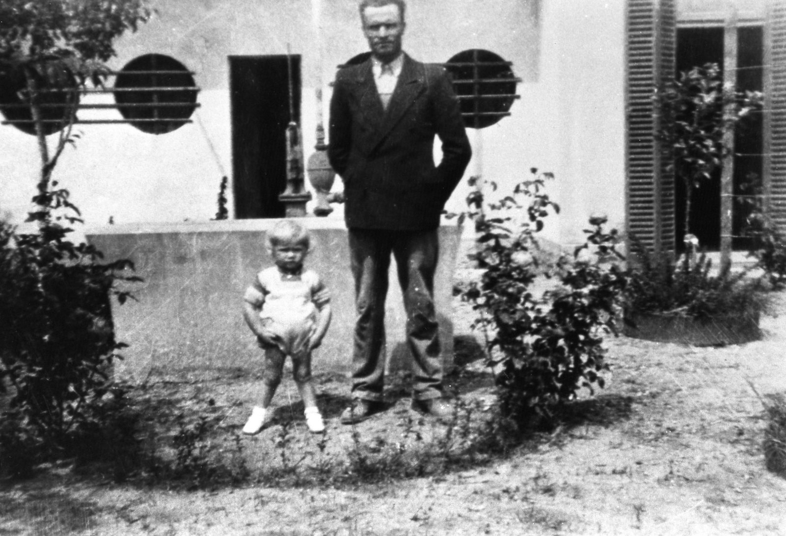A young Luis standing with his father, Luis Palau Sr., outside their home in Ingeniero Maschwitz, Argentina (1937).