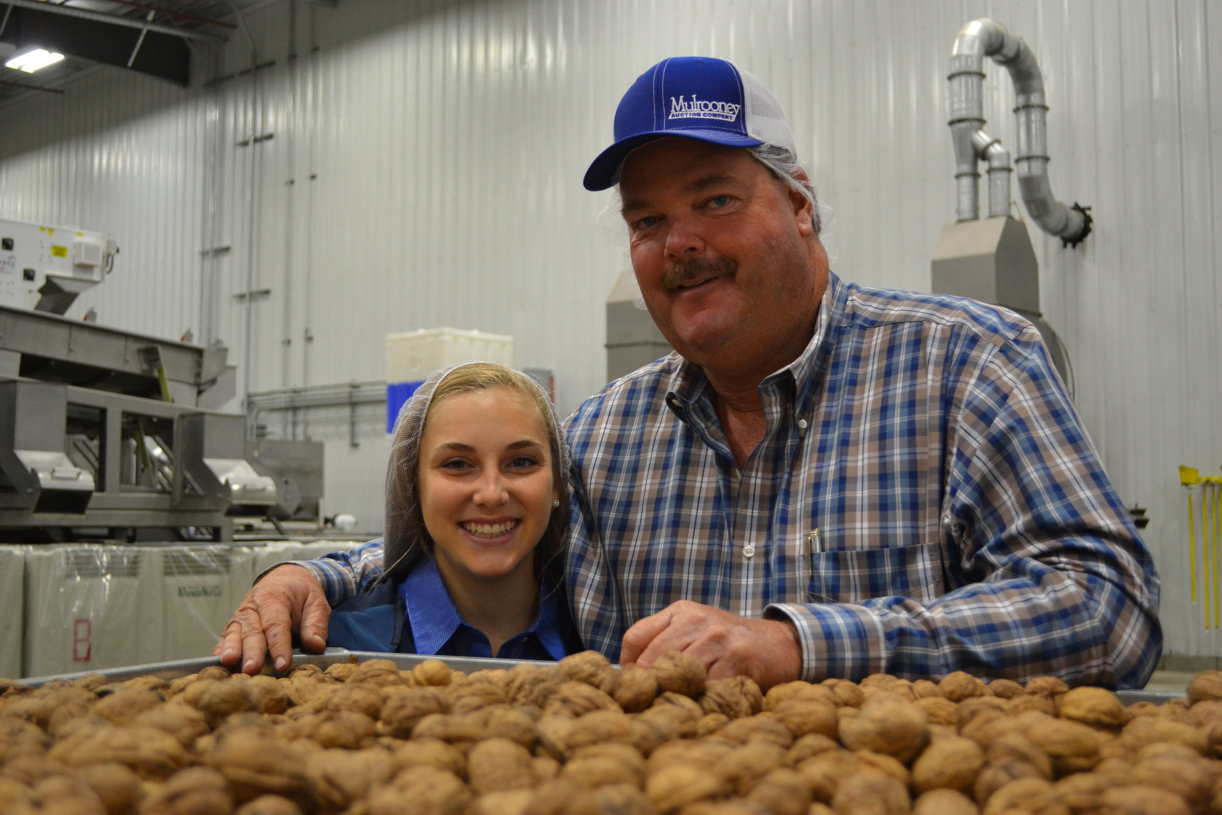 H A R V E S T: Kenny, Elisabeth's dad, is pictured along side the Farm Girl Chef herself in a walnut processing facility in Linden, California. The two were showing a television reporter around the facility, sharing the process the commodity travels through before ending up in a grocery store.
