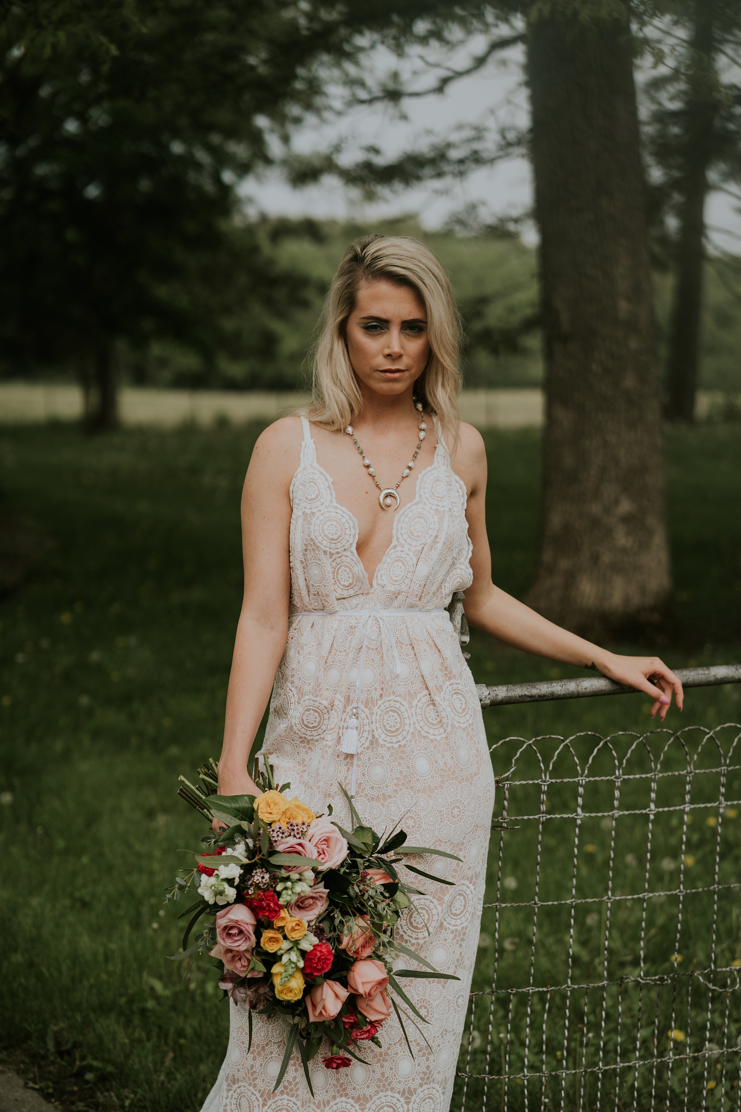 Bride stands at fence in front of old church in Iowa, wears boho style wedding gown and holds pink and cream bouquet