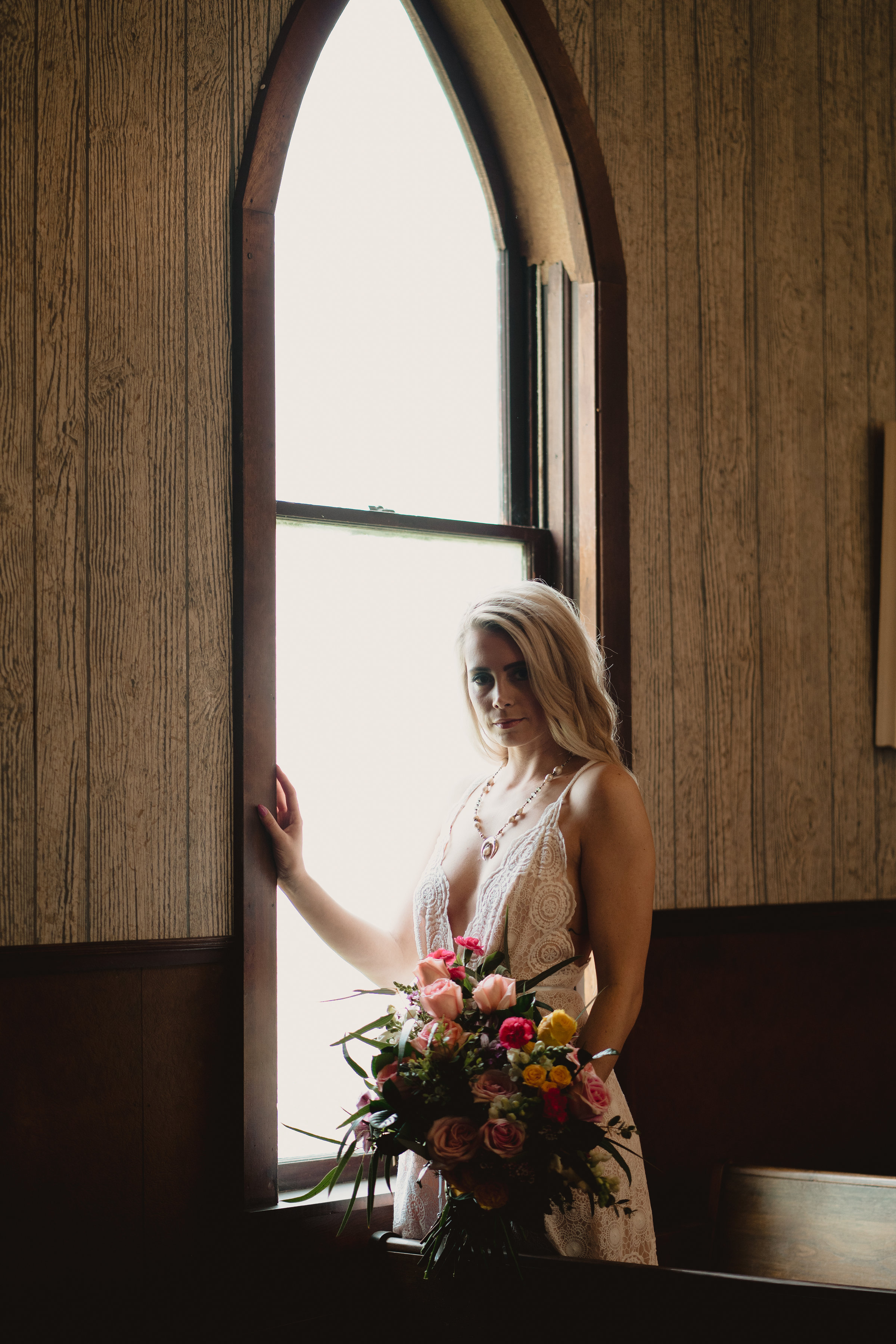 bride wears vintage style gown, stands in front of window of old church in Iowa, holding bouquet from Lavender Blue