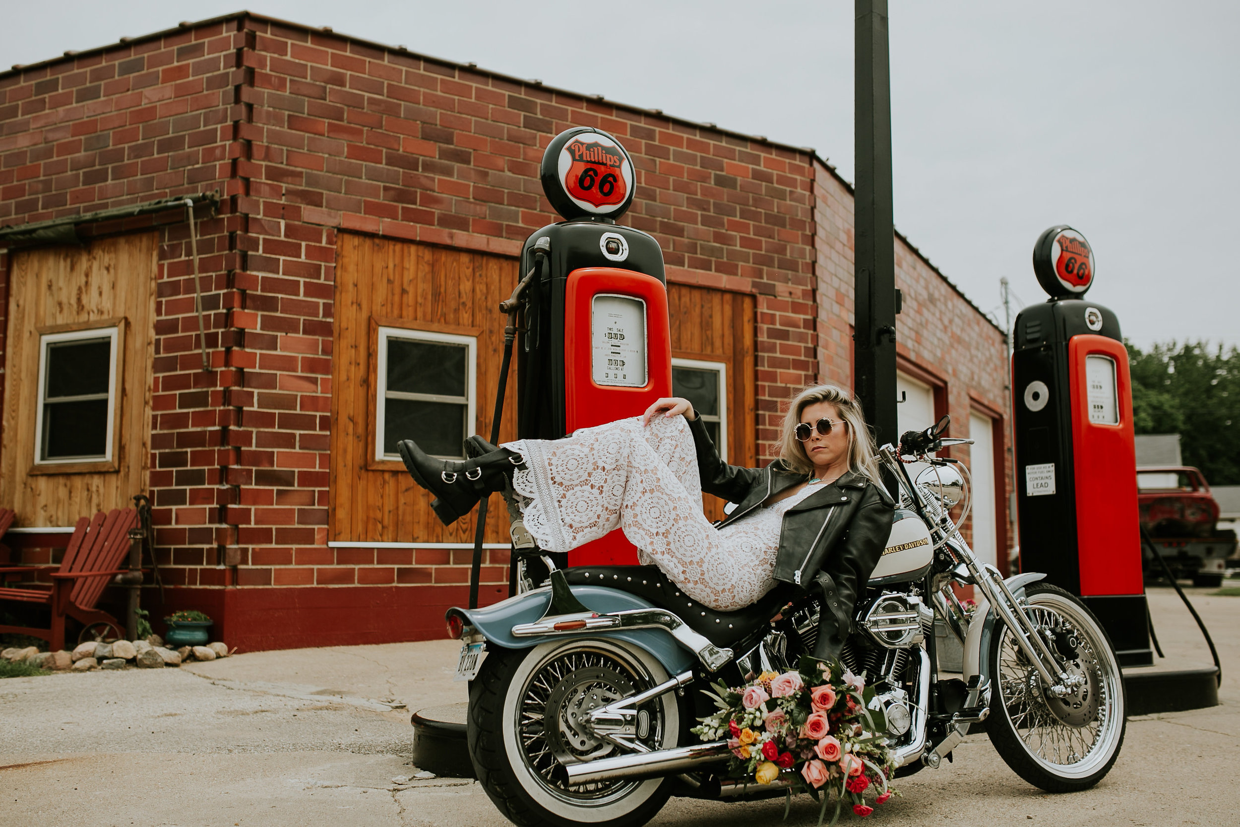 bride rests on motorcycle at old gas station in Iowa, with leather jacket , holding flowers from Lavender Blue