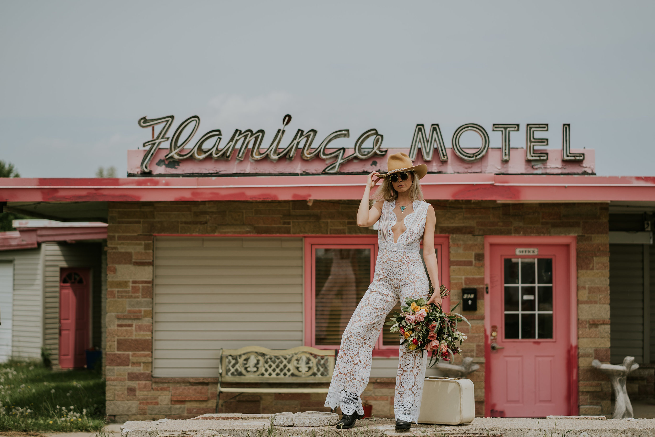 Bride wears boho wedding pants suit, hold flowers from Lavender Blue, in front of old motel in Iowa