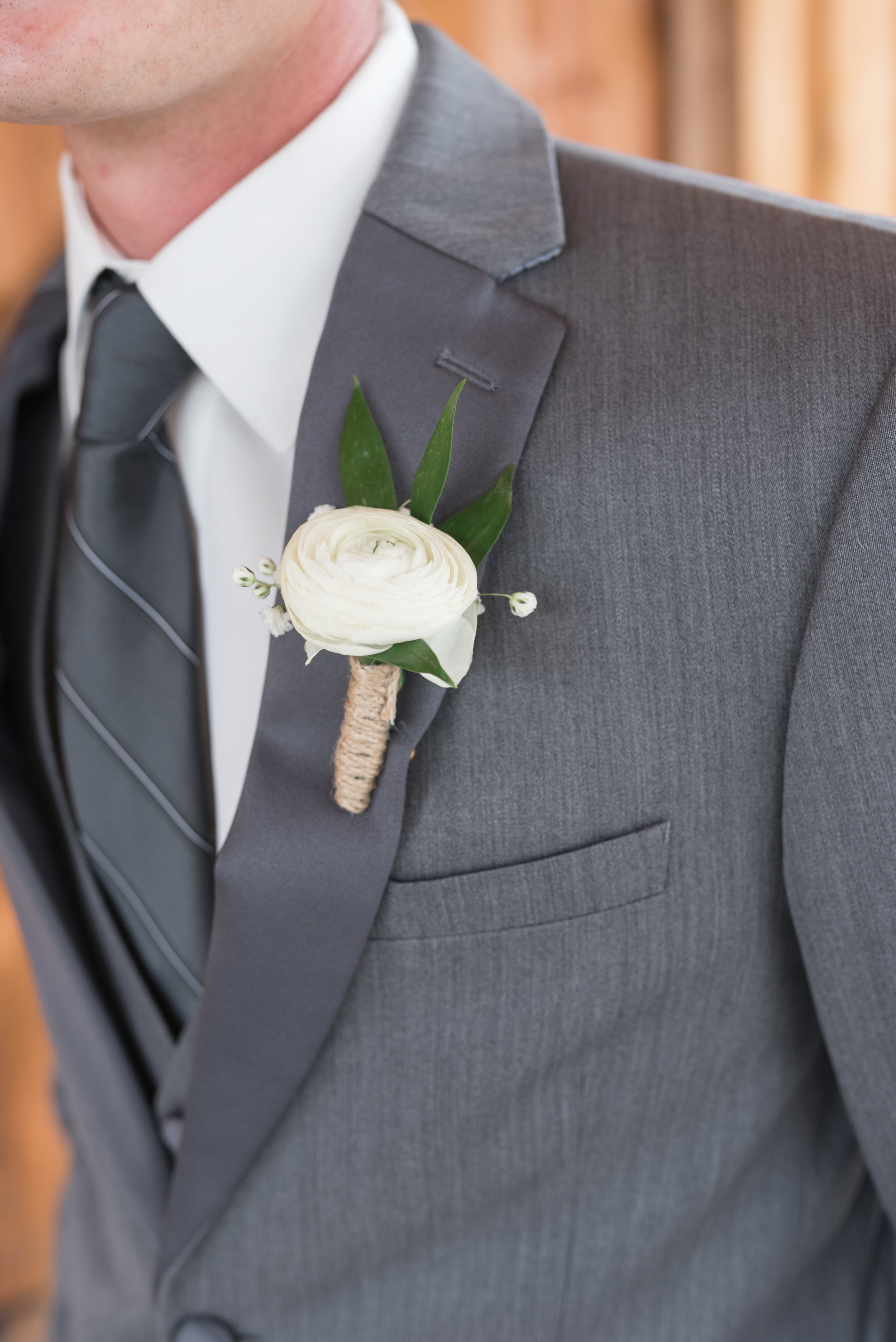 groom in white boutonniere and grey wedding suit and tie // des moines wedding flowers