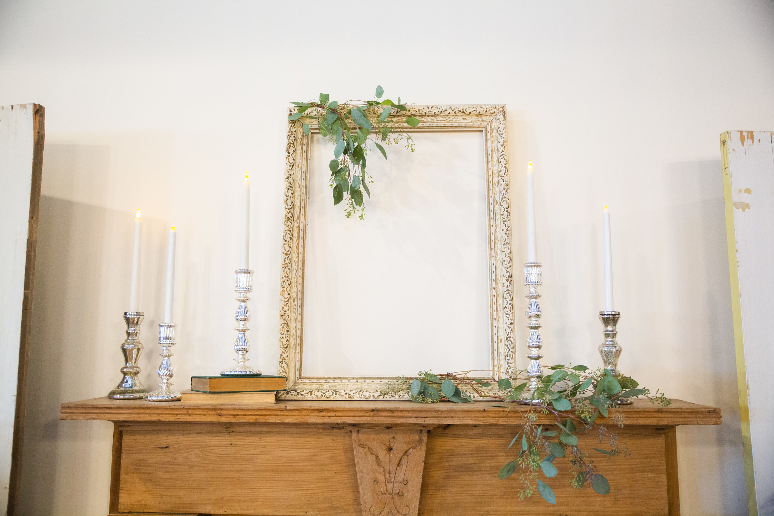 eucalyptus decor and tall silver candlesticks with gold photo frames Des Moines wedding rentals