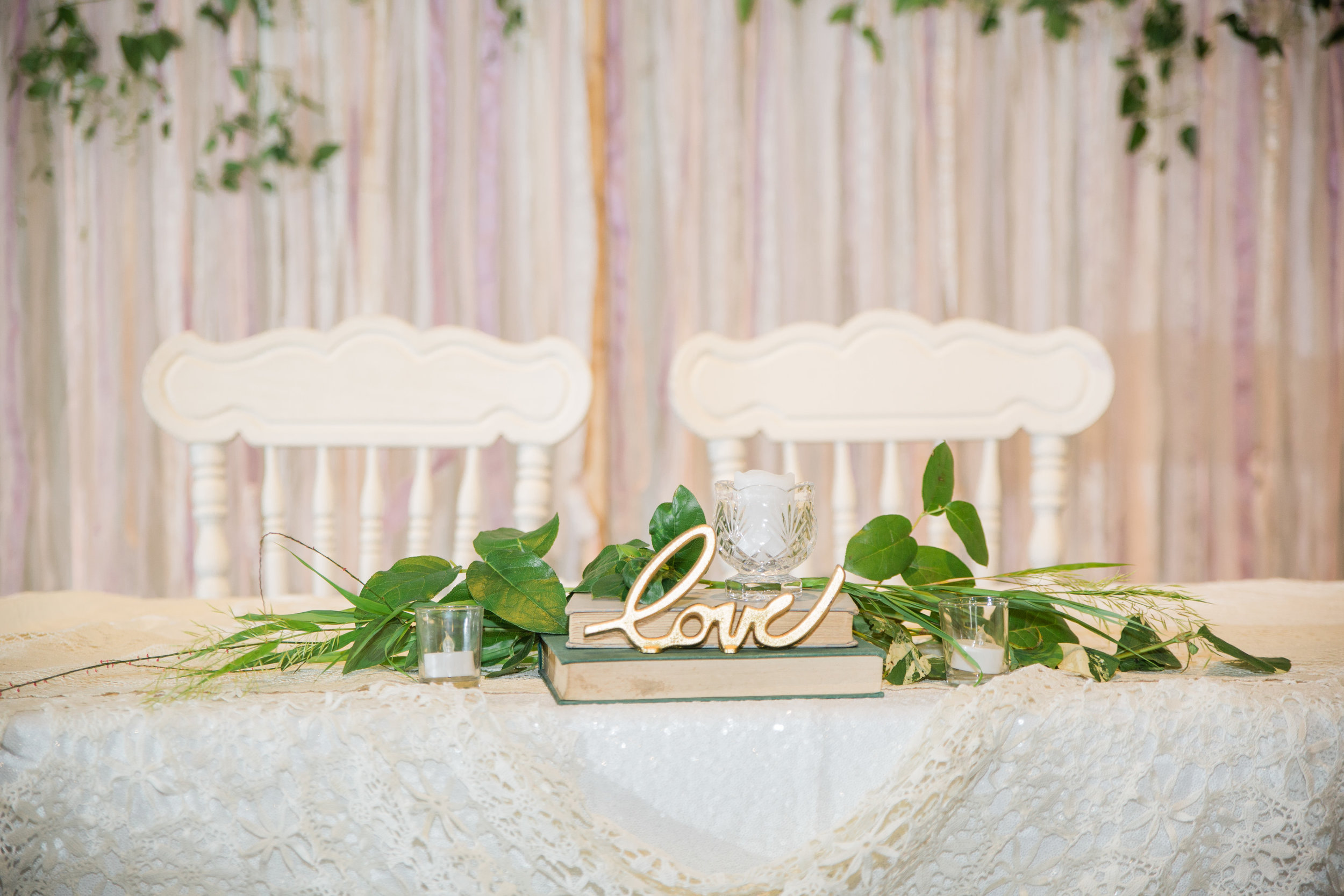 des moines wedding florists and rentals // white themed wedding decor with candles and old books and vintage white chairs