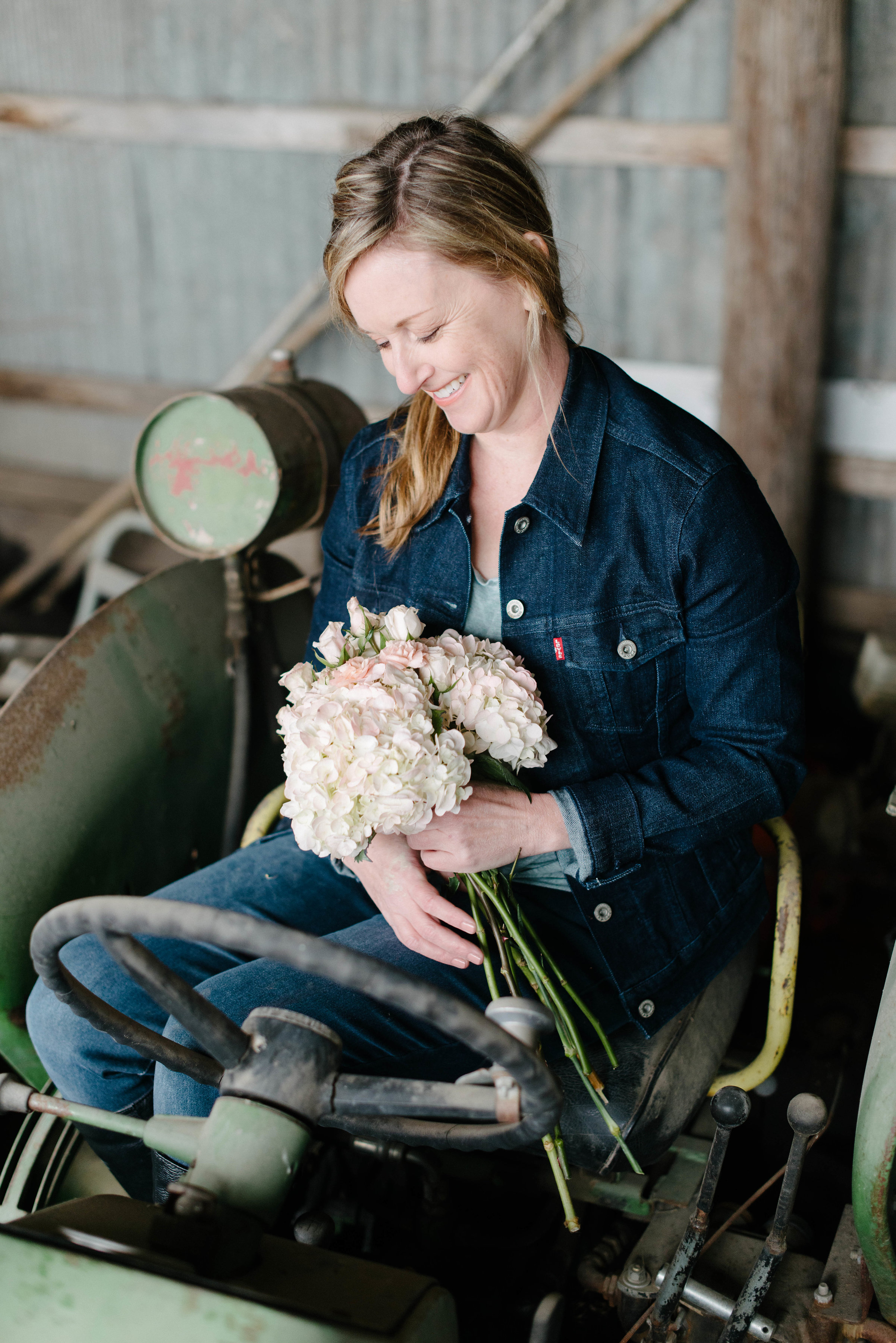 Lynda, a Des Moines wedding florist, in a natural barn setting with flowers Lavender Blue Floral