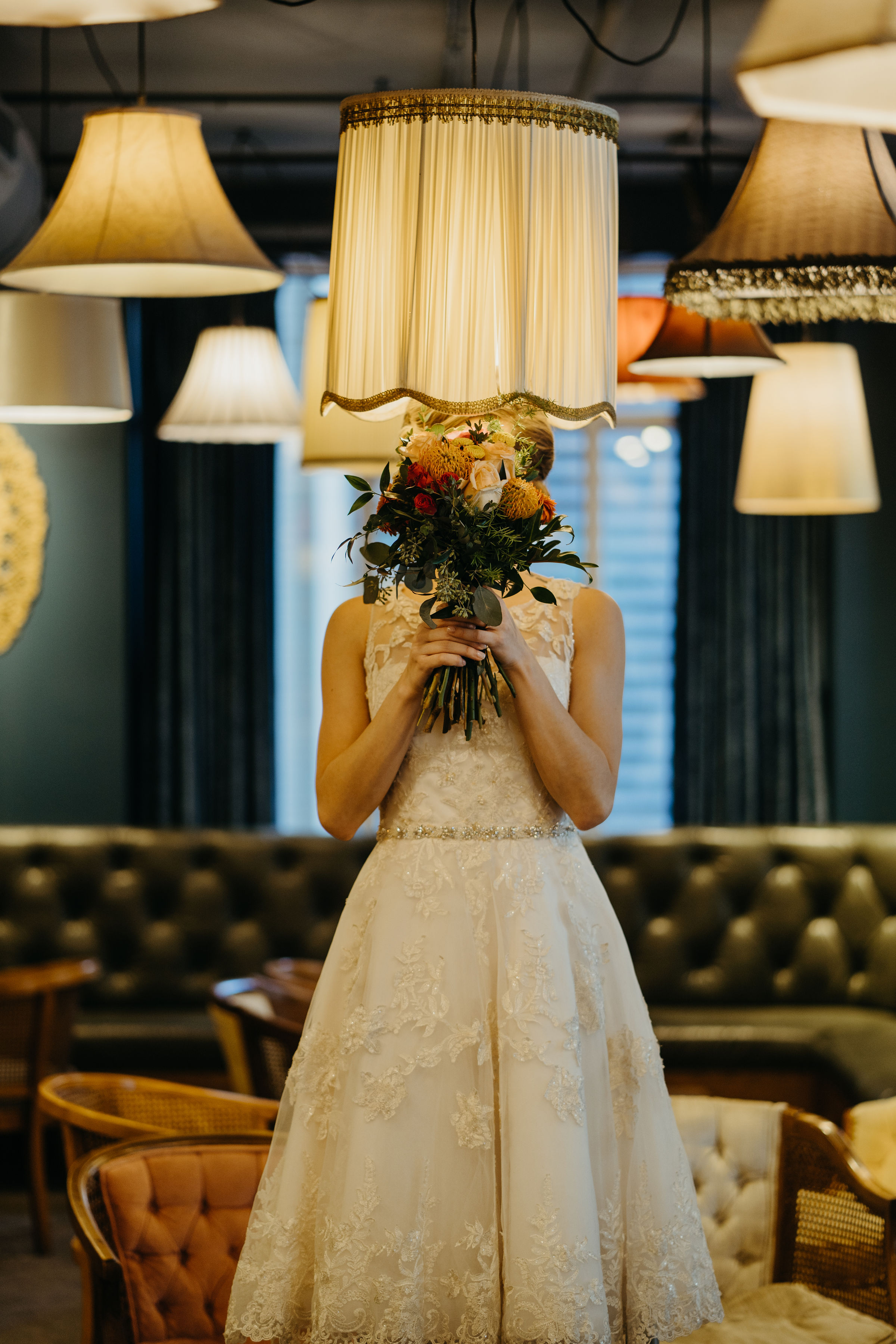 Bride wears a lace and satin retro-style wedding dress and it has a gold thin band at waist, bride stands under a vintage lampshade at a fancy bar and holds up her flowers from Lavender Blue
