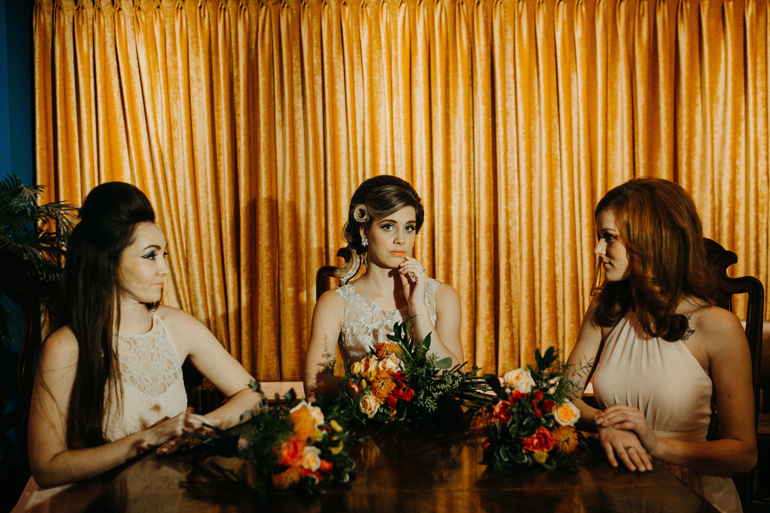 bridesmaids and bride sit at a large table in fancy des moines bar and rest their floral bouquets on the table in front of them, in colors of gold, red, and orange