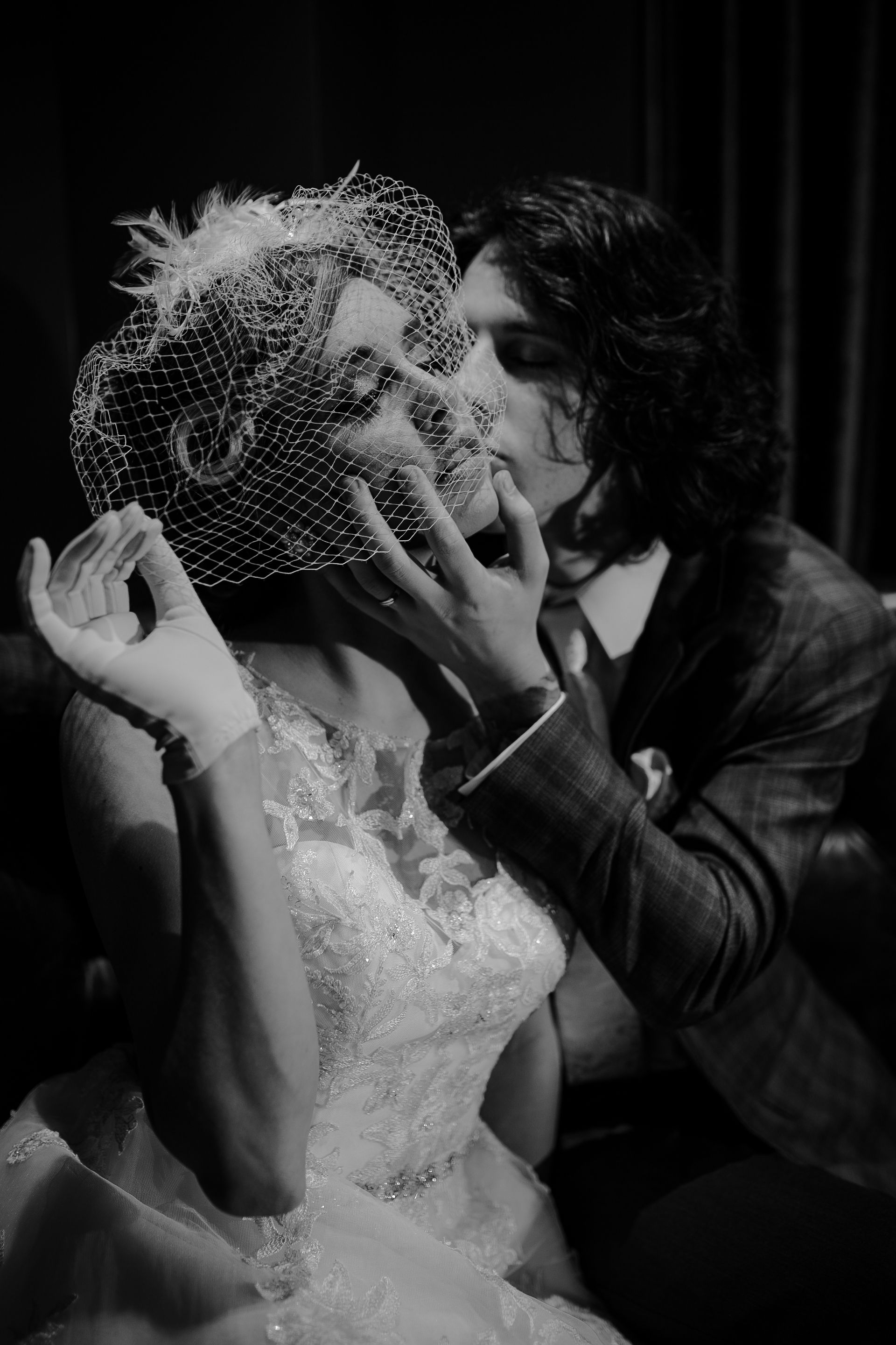 black and white image of intimate moment between bride and groom, groom kisses cheek and bride hold tulle from her vintage hat over her eyes