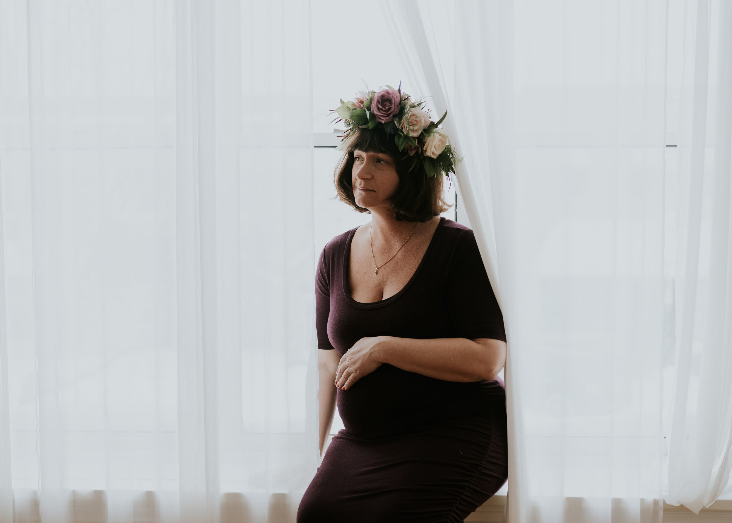pregnant mother in Des Moines wears a custom flower crown wreath of lavender roses, and cream roses, and seeded eucalyptus