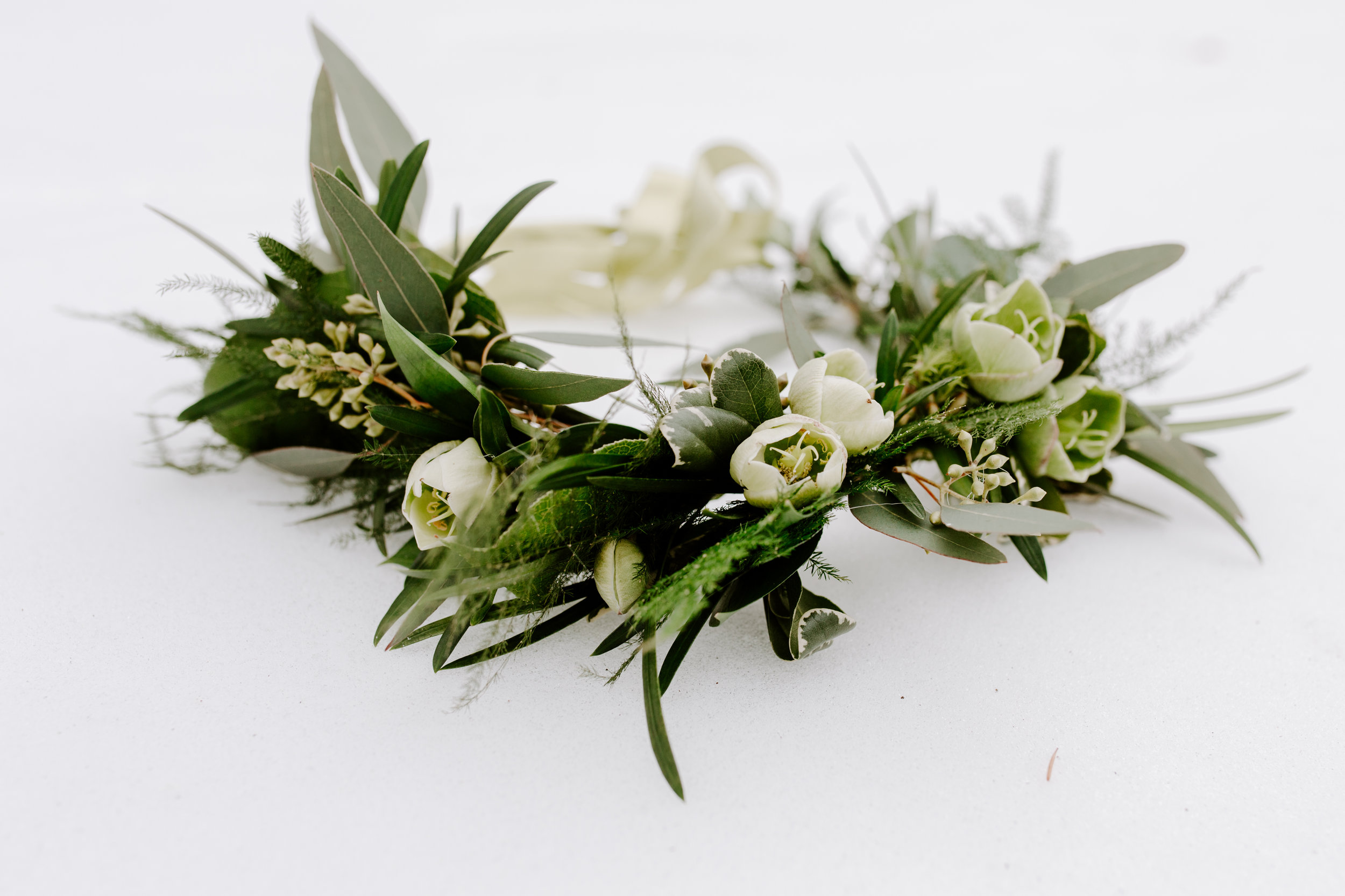 green and white flower crown with hellebore and green eucalyptus, make by Lavender Blue Floral in Des Moines Iowa, custom made flower crown to wear in weddings or photo shoot